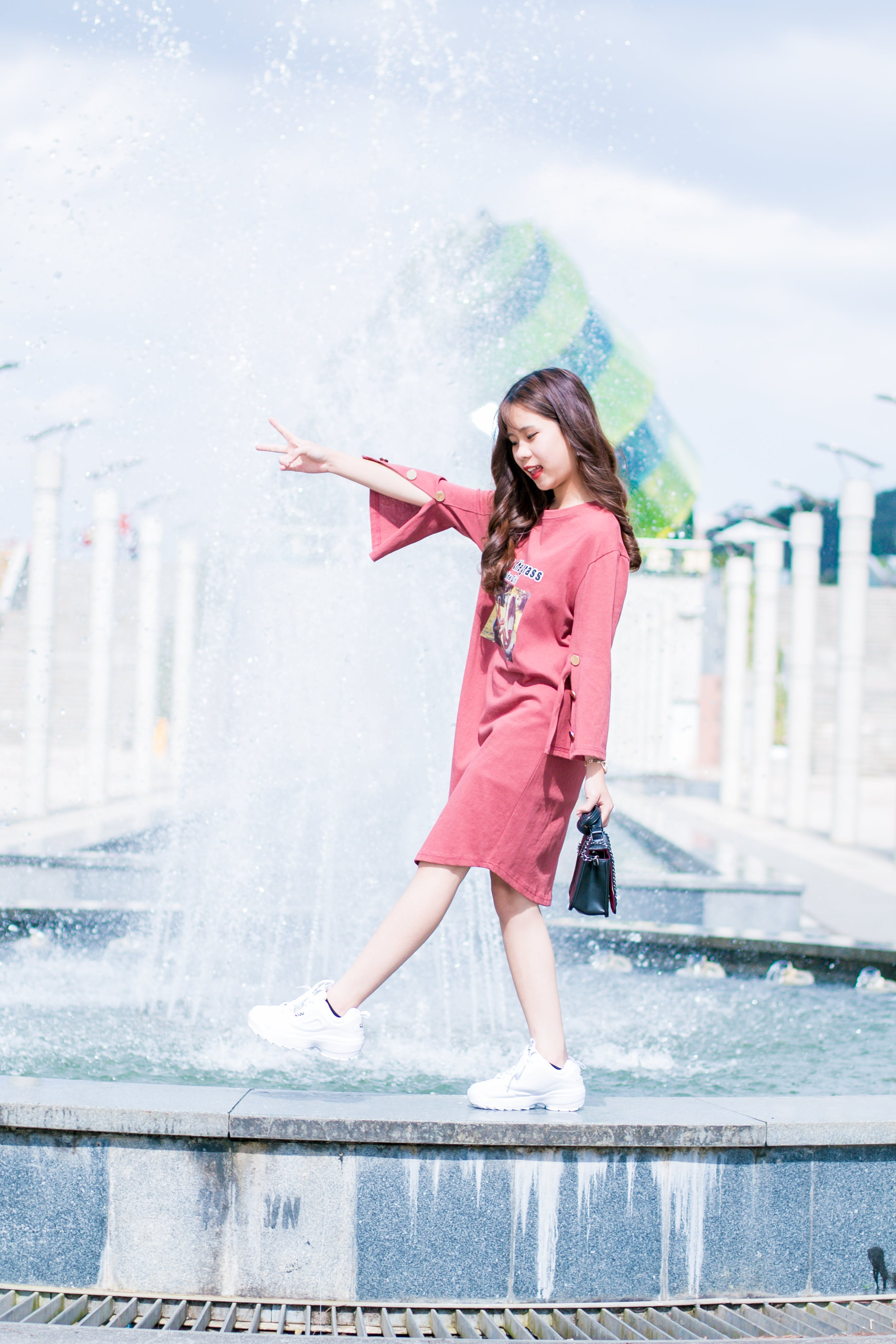 Woman Wearing Pink Long-sleeved Dress Walking on Fountain during Daytinme