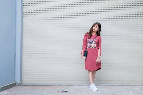 Standing Woman Wearing Red Dress Beside Roll Top Door