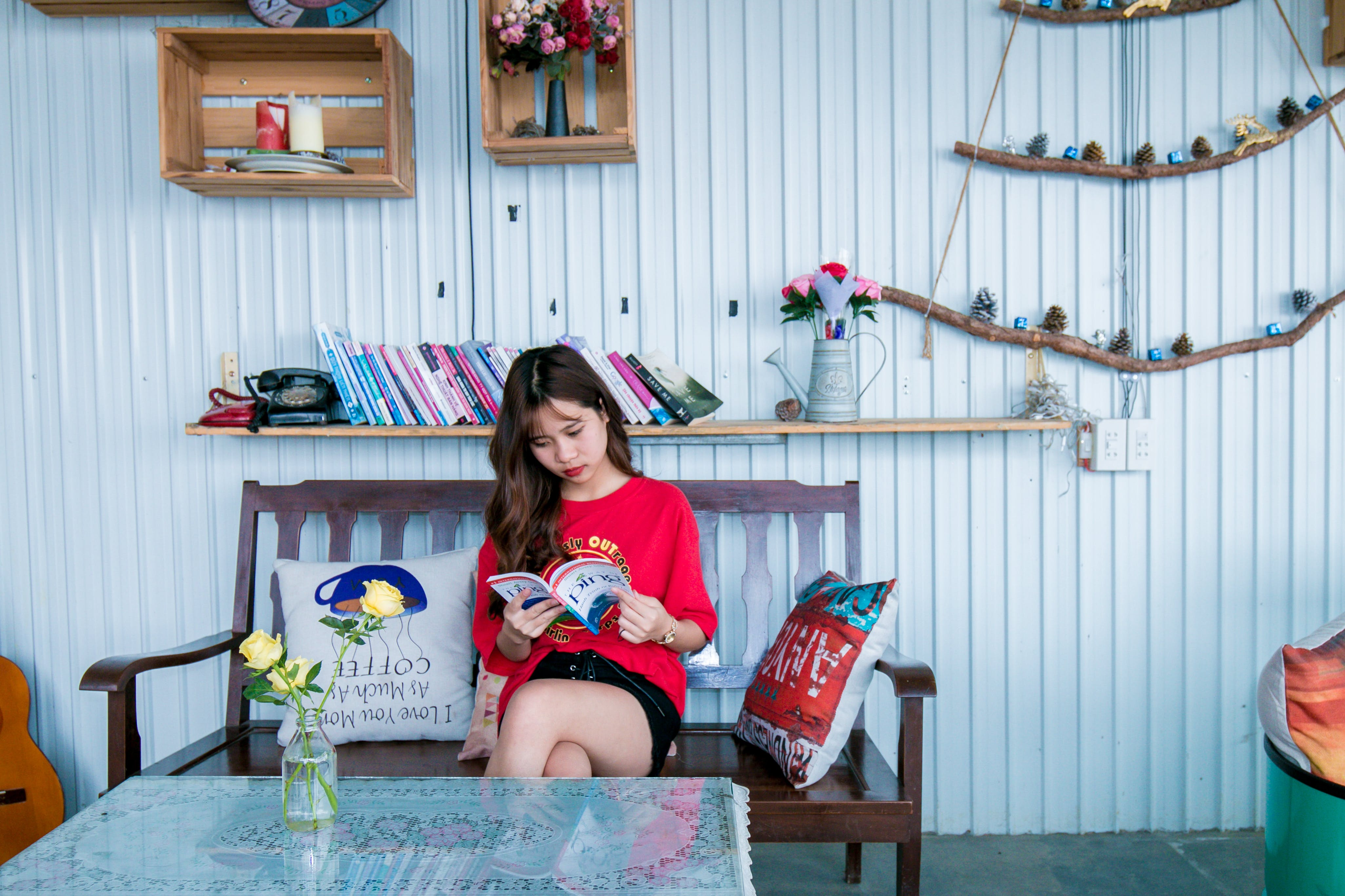Woman in Red Shirt Reading Book While Sitting on Bench