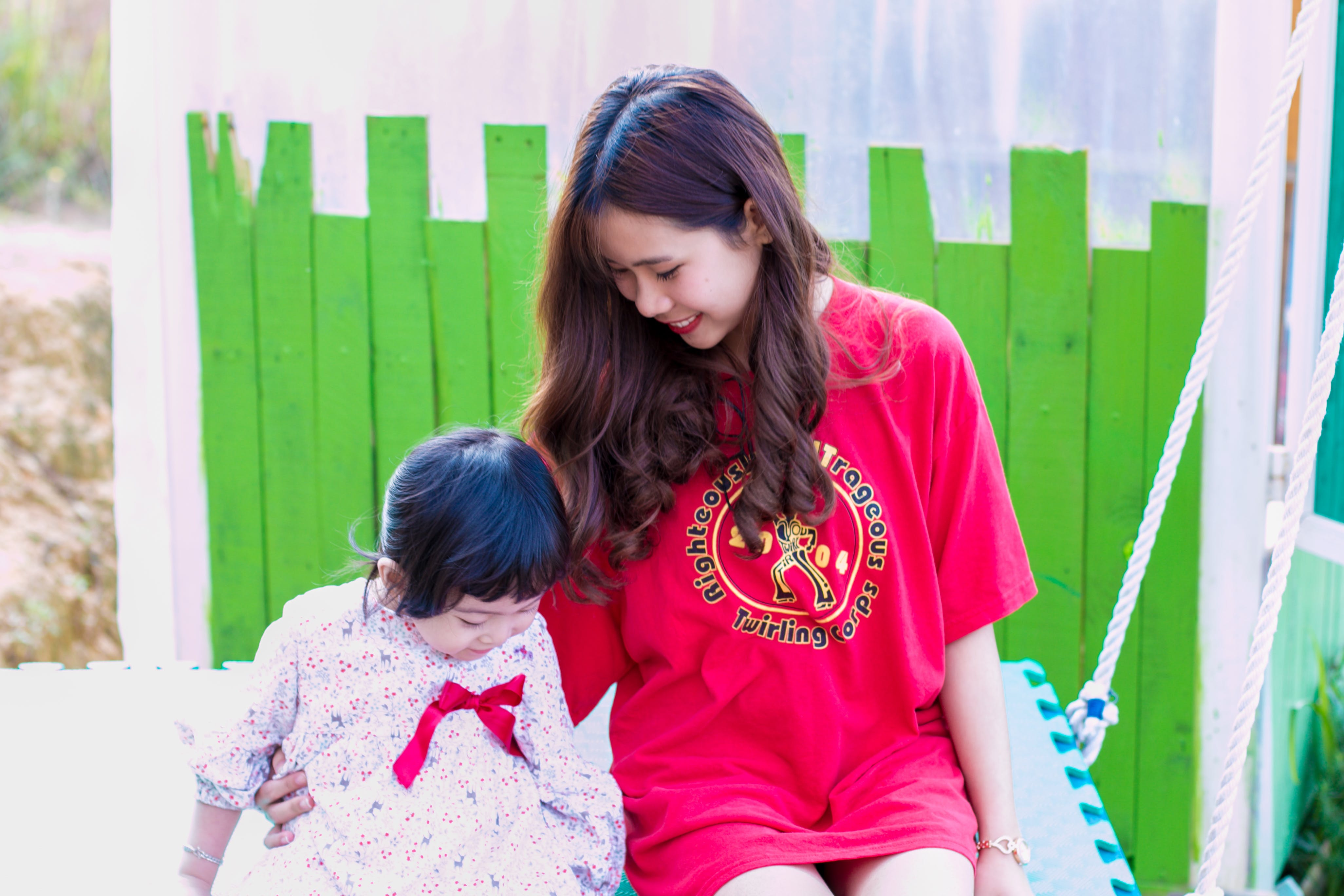 Woman in Red T-shirt Sitting Beside Girl
