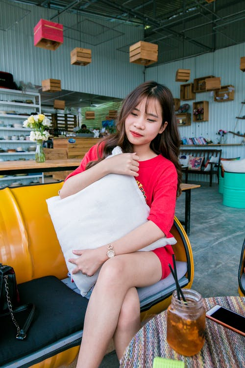 Smiling Woman Wearing Red Lipstick and Red Shirt Holding White Throw Pillow