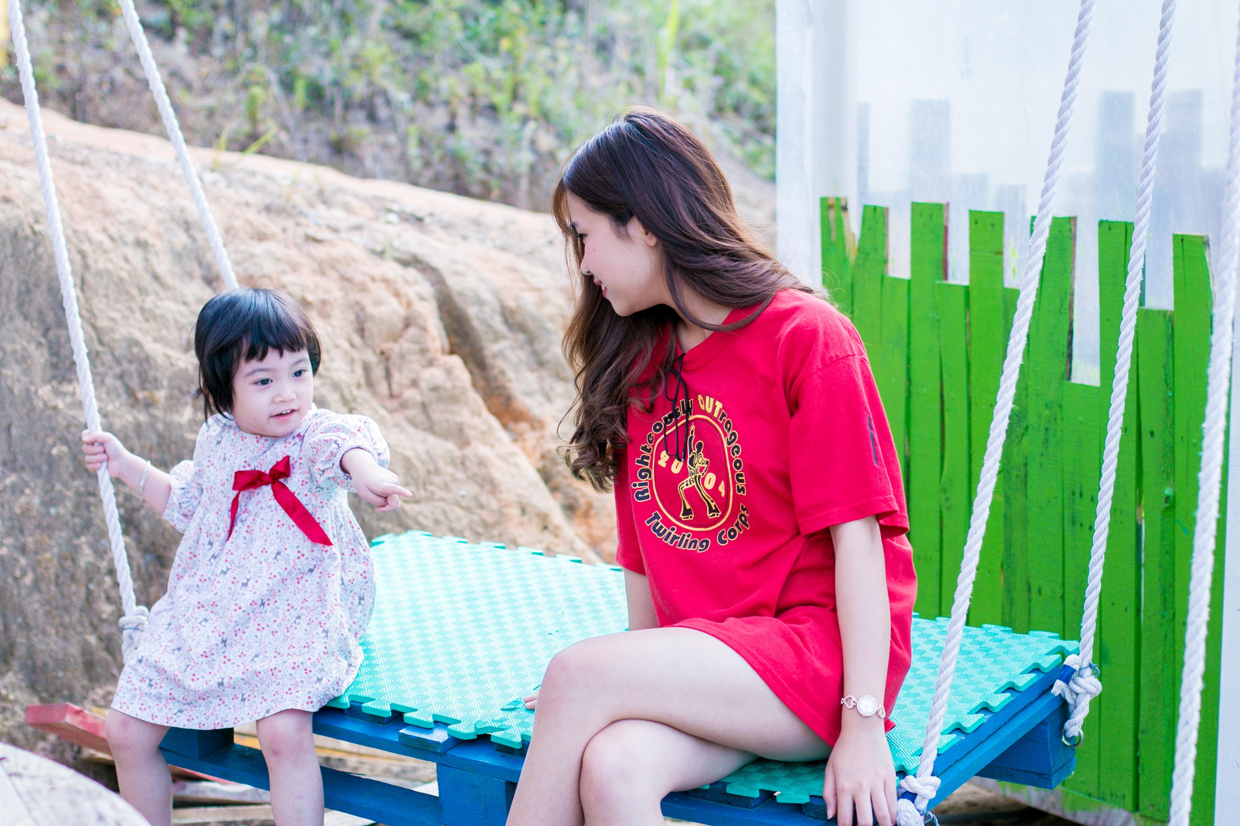 Woman Wearing Red Crew-neck Shirt Sitting on Swing Bench