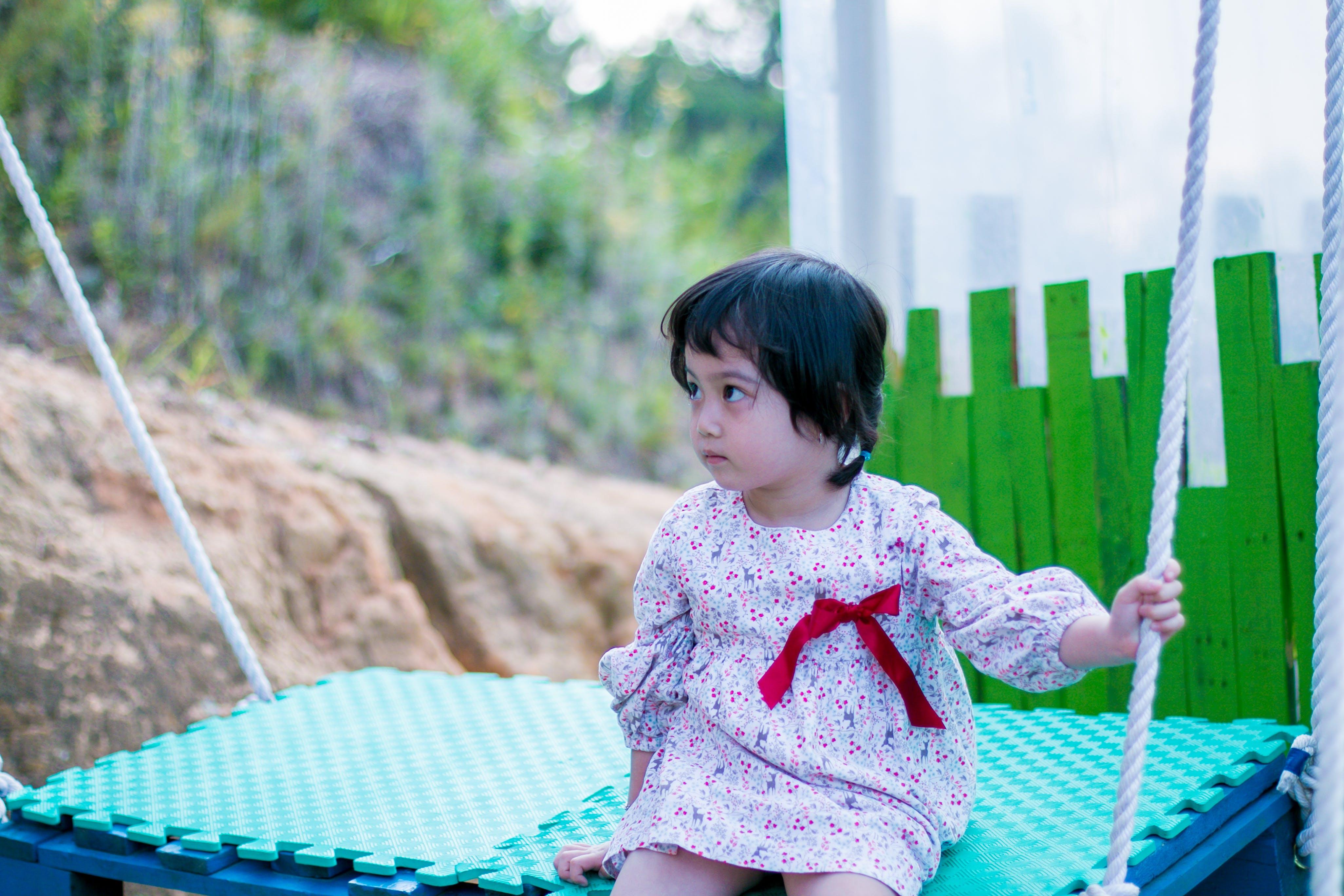 Girl Wearing White Long-sleeved Dress While Sitting on Swing