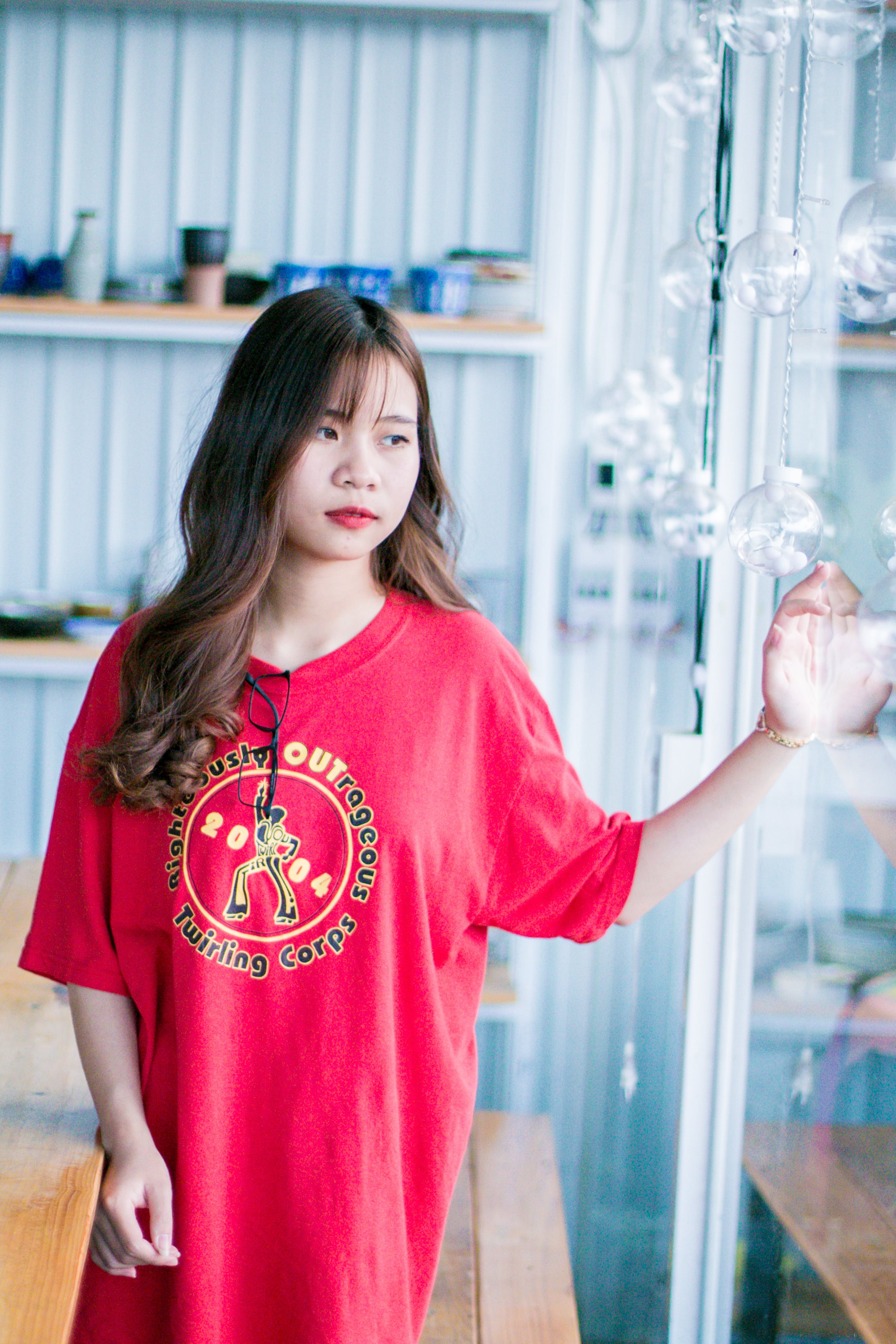 Woman Wearing Red Shirt Standing Near Glass Hanging Decor