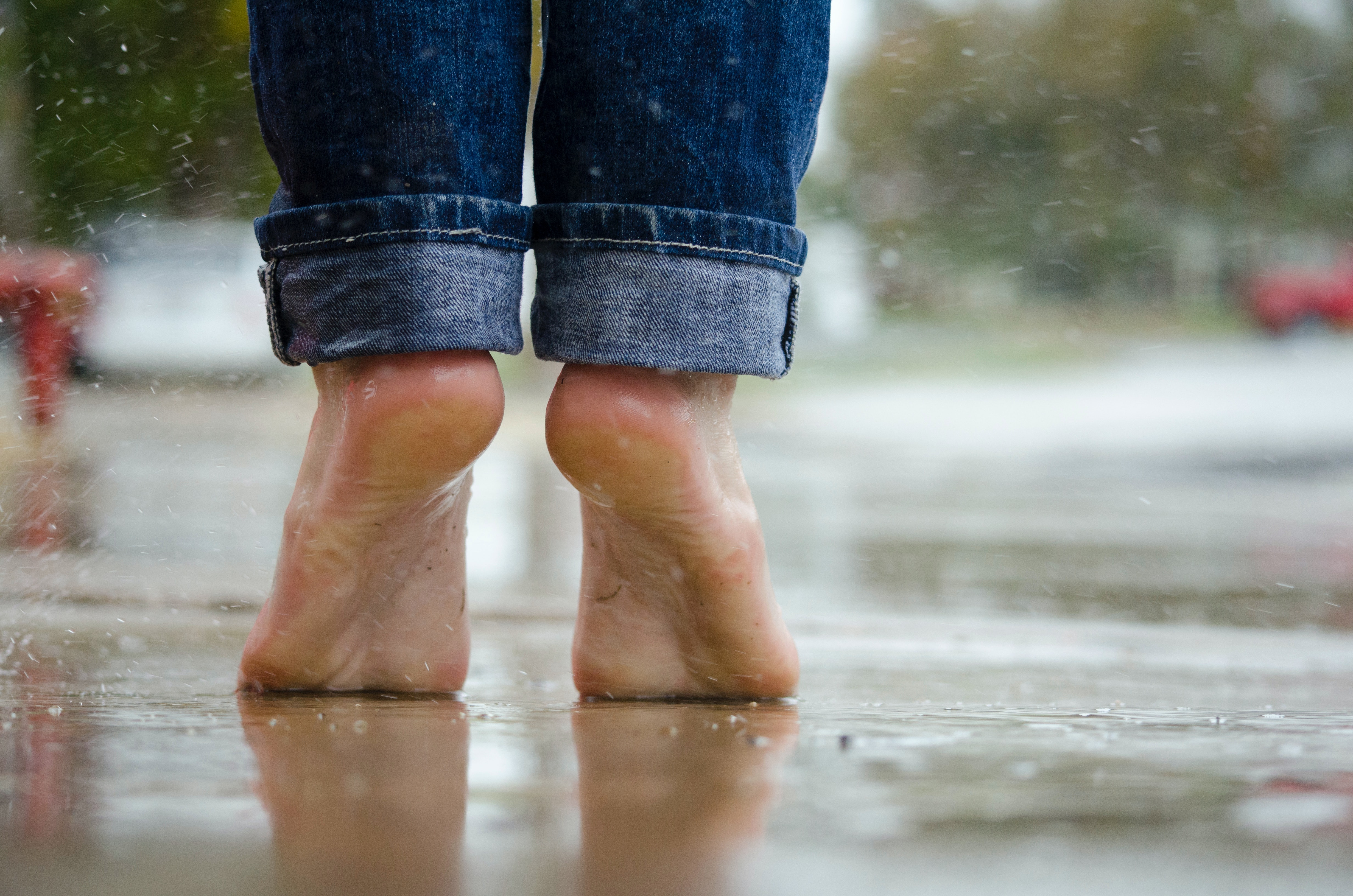 Person In Blue Denim Jeans Standing Outside The Rain