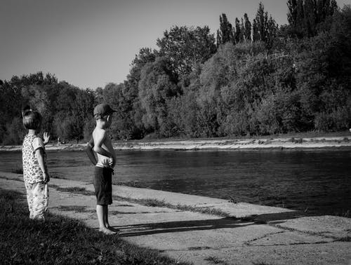 Grayscale Photo of Oy Boy and Girl Standing Near Body of Water