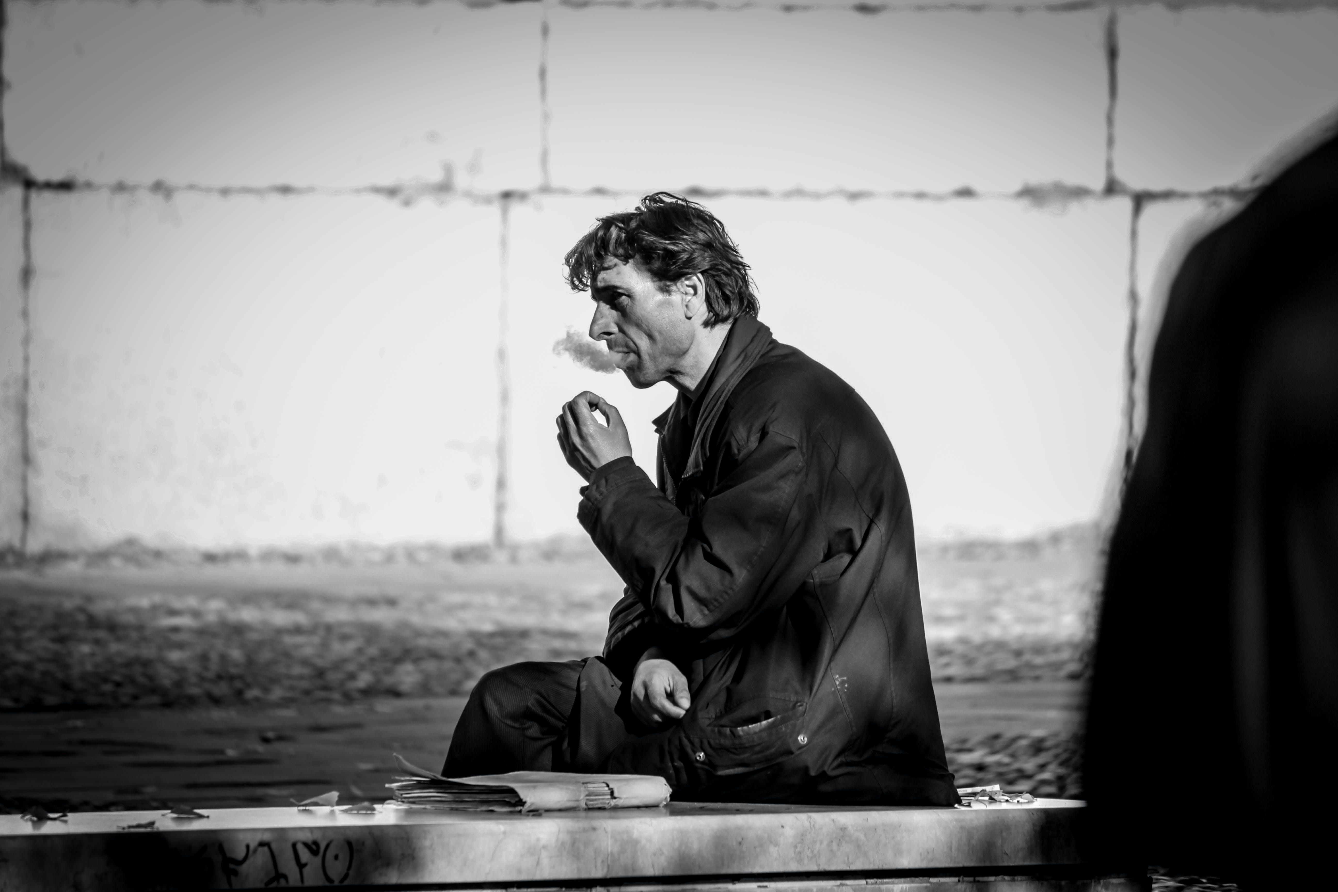 Grayscale Photo of Smoking Man While Sitting on Bench