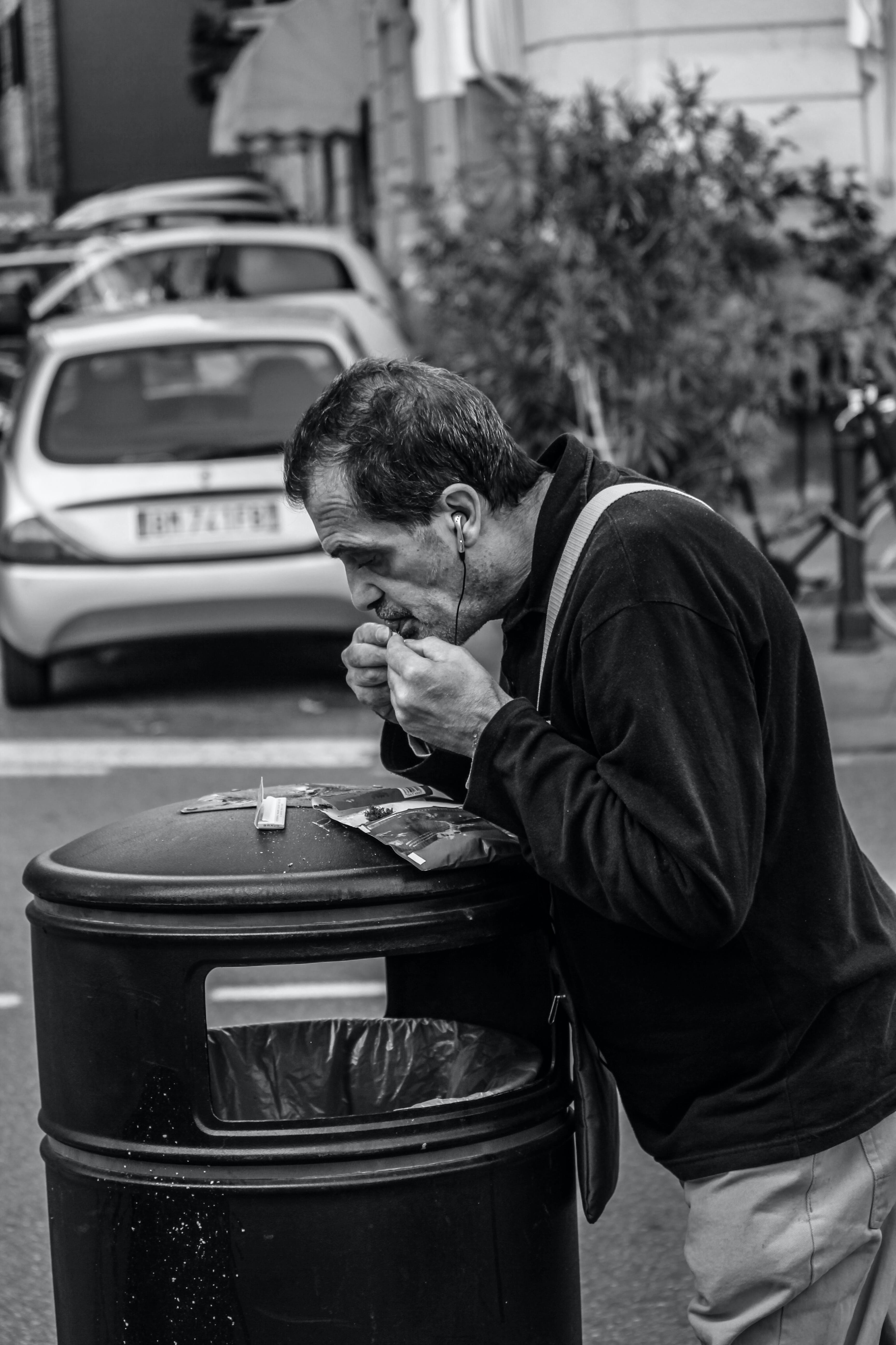 Grayscale Photography of Man Leaning on Black Trash Bin