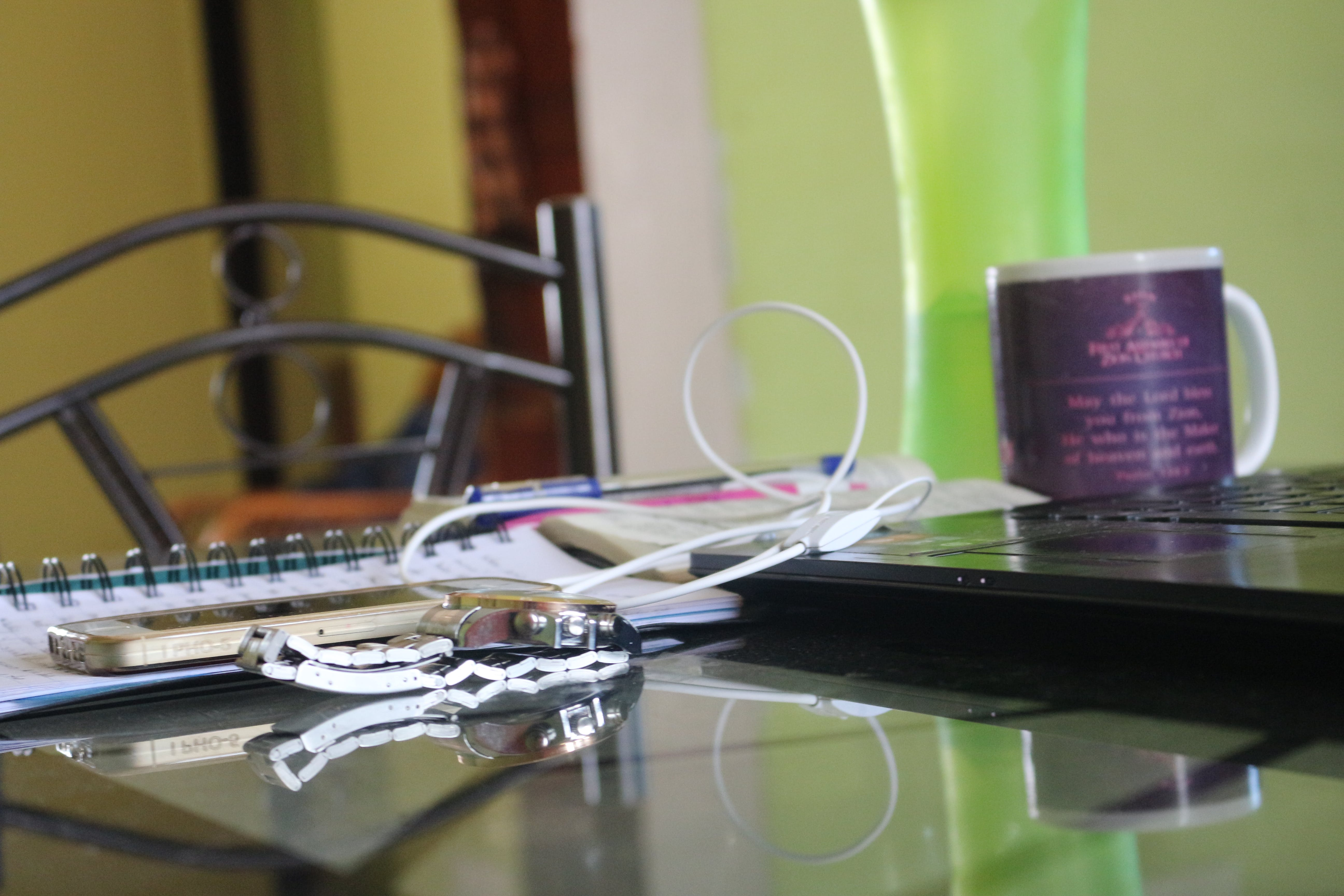 Round Silver-colored Watch With Link Band on Top of Table Beside Black Laptop Computer