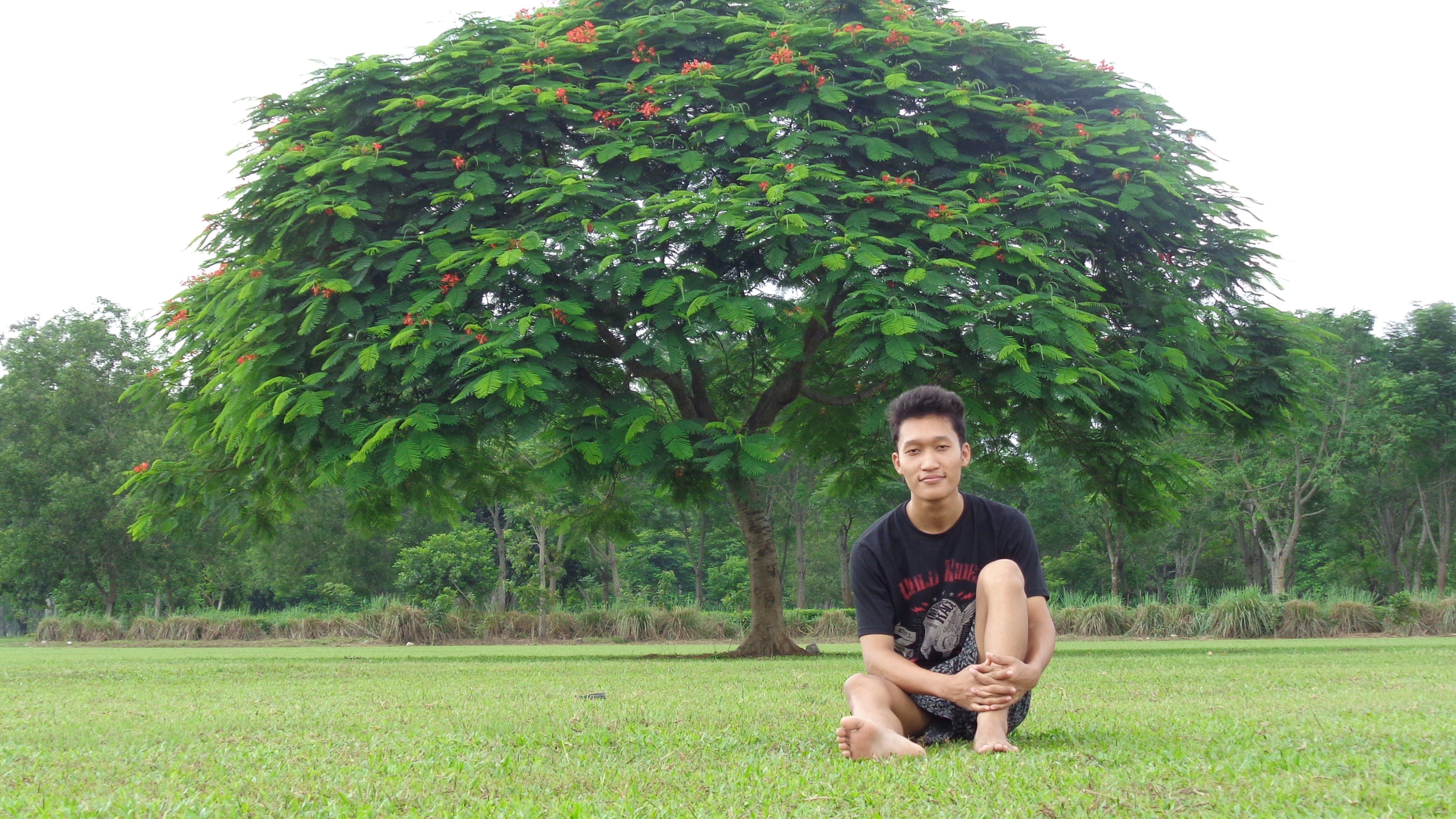 Man in Black Shirt Sitting on Grass Field