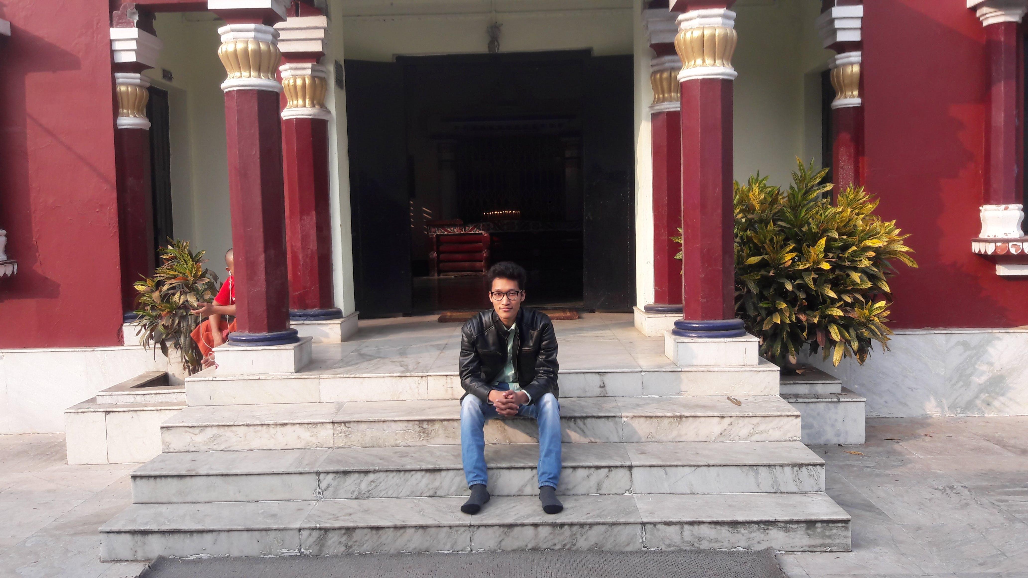 Man Sitting on Staircase Beside Red Pillars