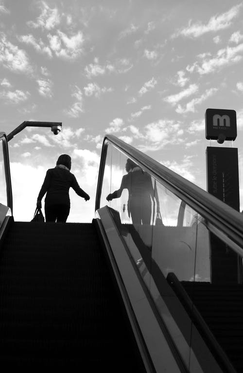Silhouette of Person on Top of Escalator