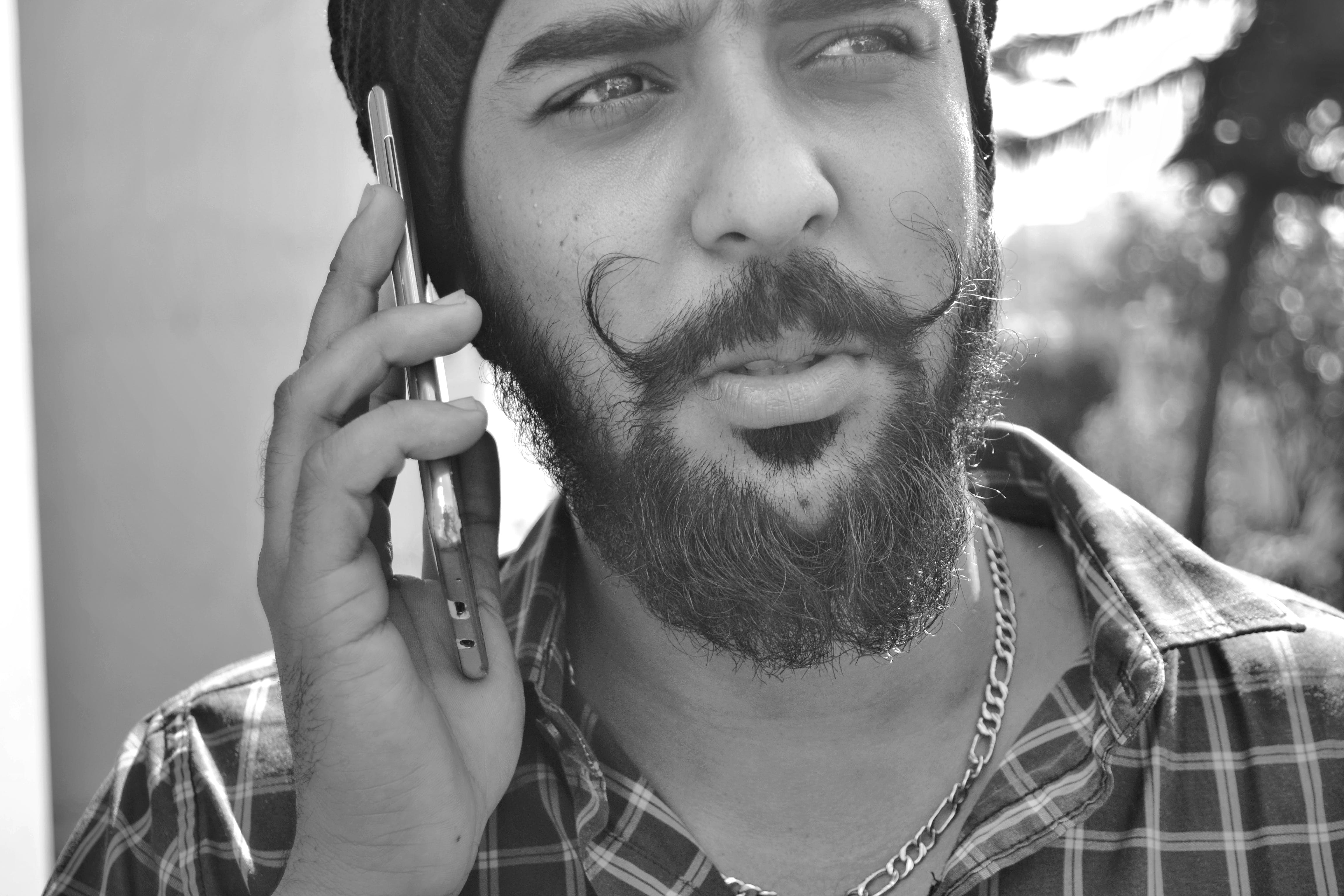 Grayscale Portrait Photo of Man Holding Phone