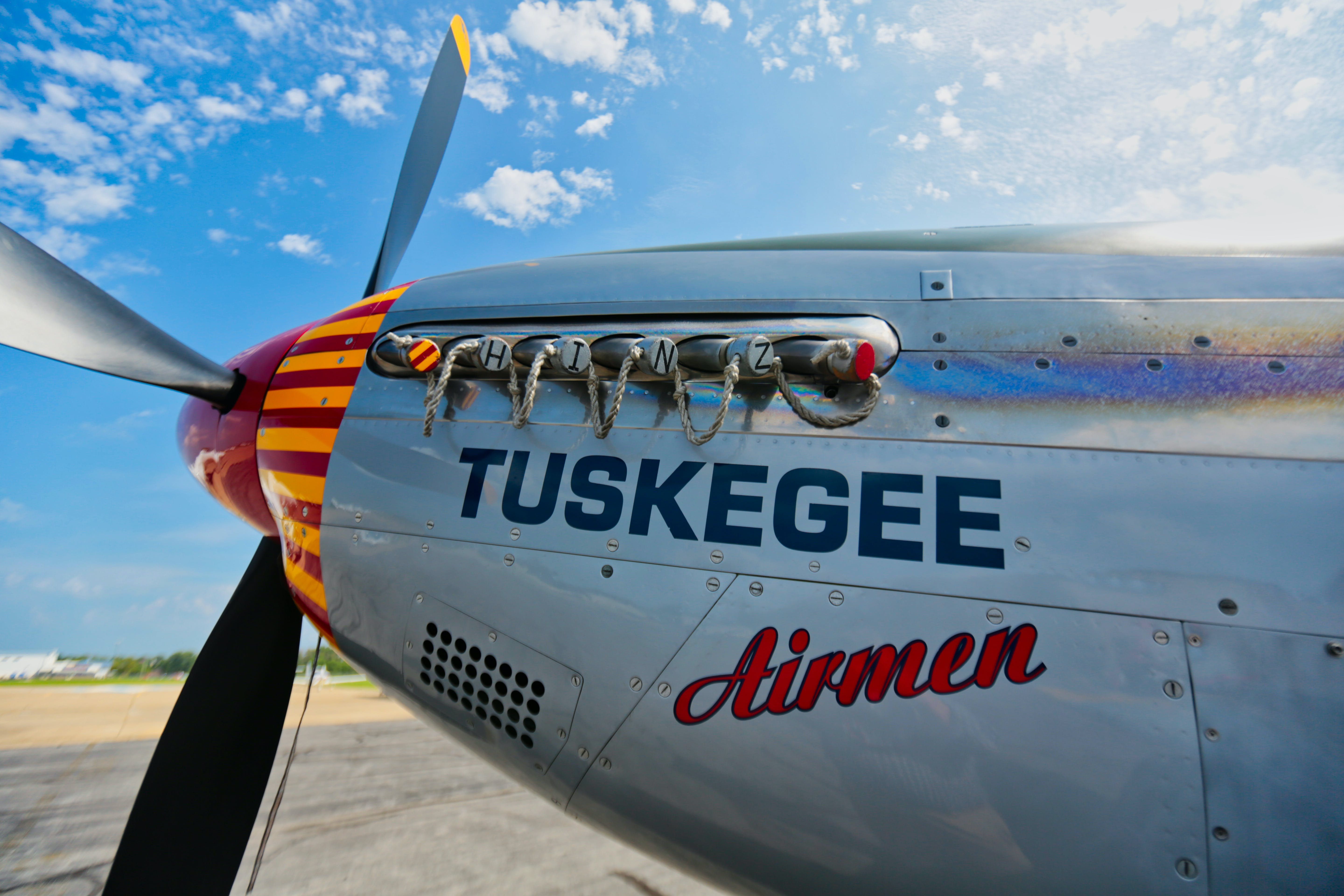 Gray Tuskegee Airmen Airplane Under Blue and White Cloudy Skies at Daytime