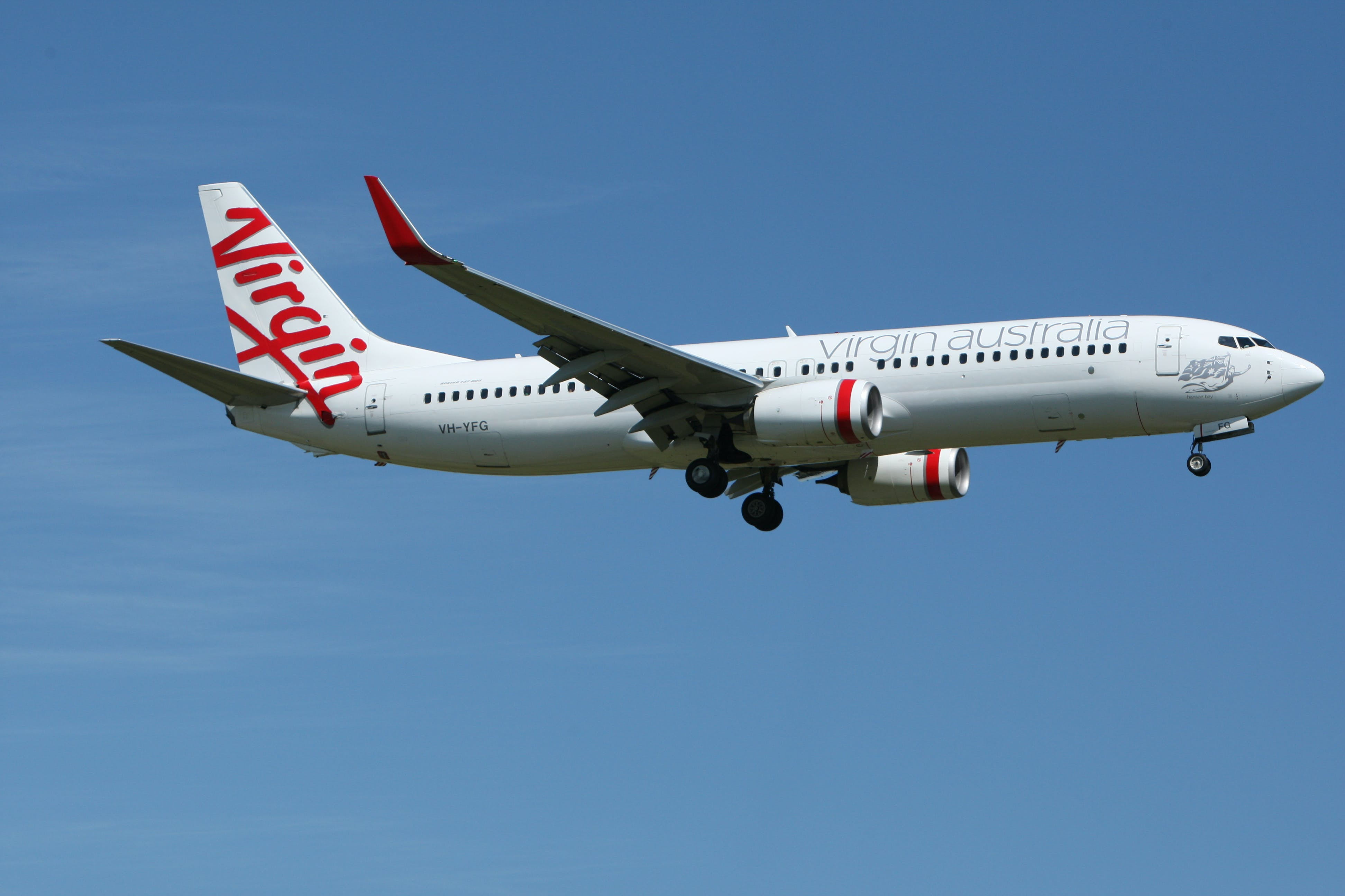 White and Red Virgin Australia Airplane Mid Air Under Blue and White Sky during Daytime