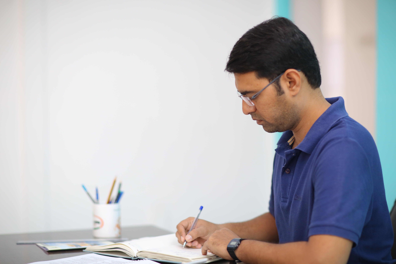Man in Blue Polo Shirt Writing