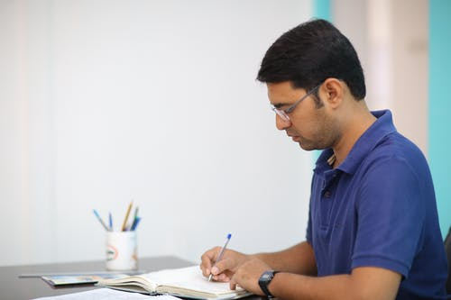 Man in Blue Polo Shirt Writing