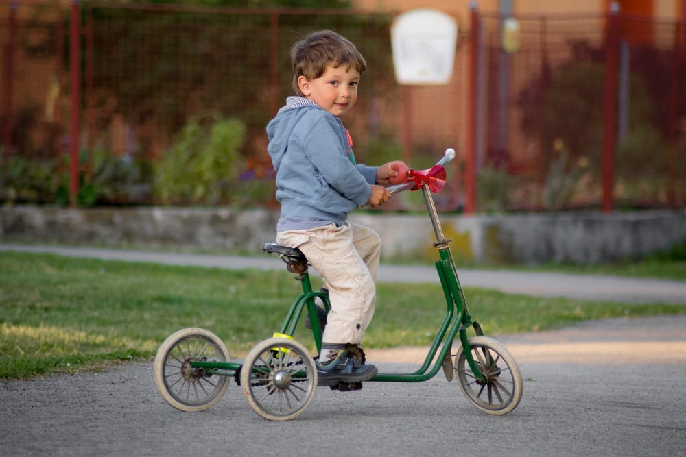 Little boy riding a green bike. | Photo: Pexels