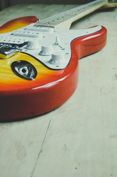 Brown and Yellow Sunburst Electric Guitar on White Tiled Flooring
