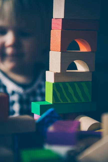 Selective Focus Photography of Beige Orange Red and Green Blocks Piled Vertically