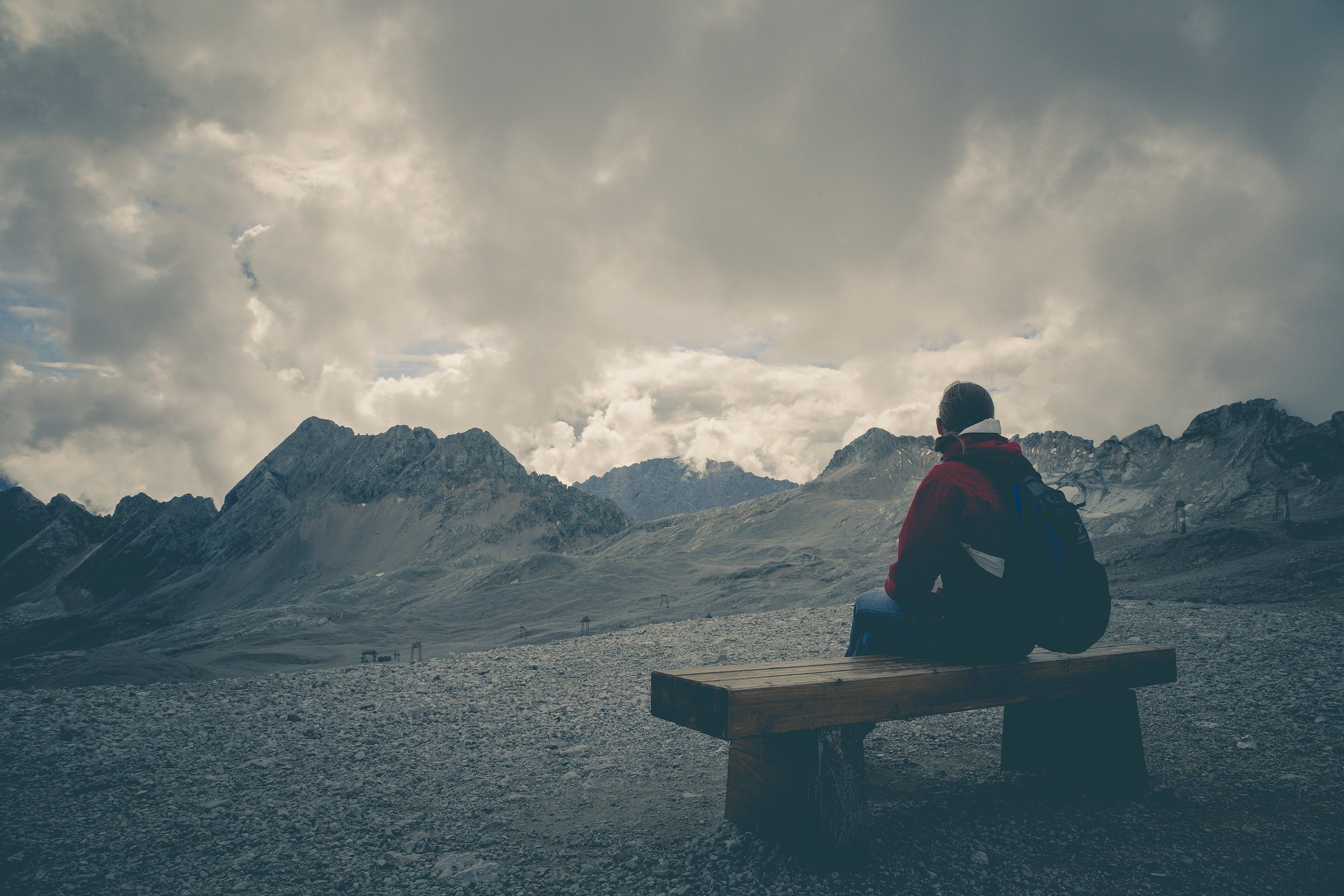 Man in Red Jacket Sitting on Brown Wooden Bench