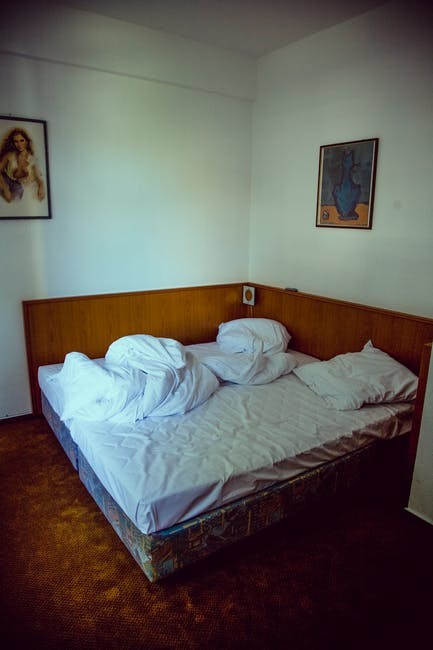 Empty Bed On Brown Floor Near Woman Painting Free Stock