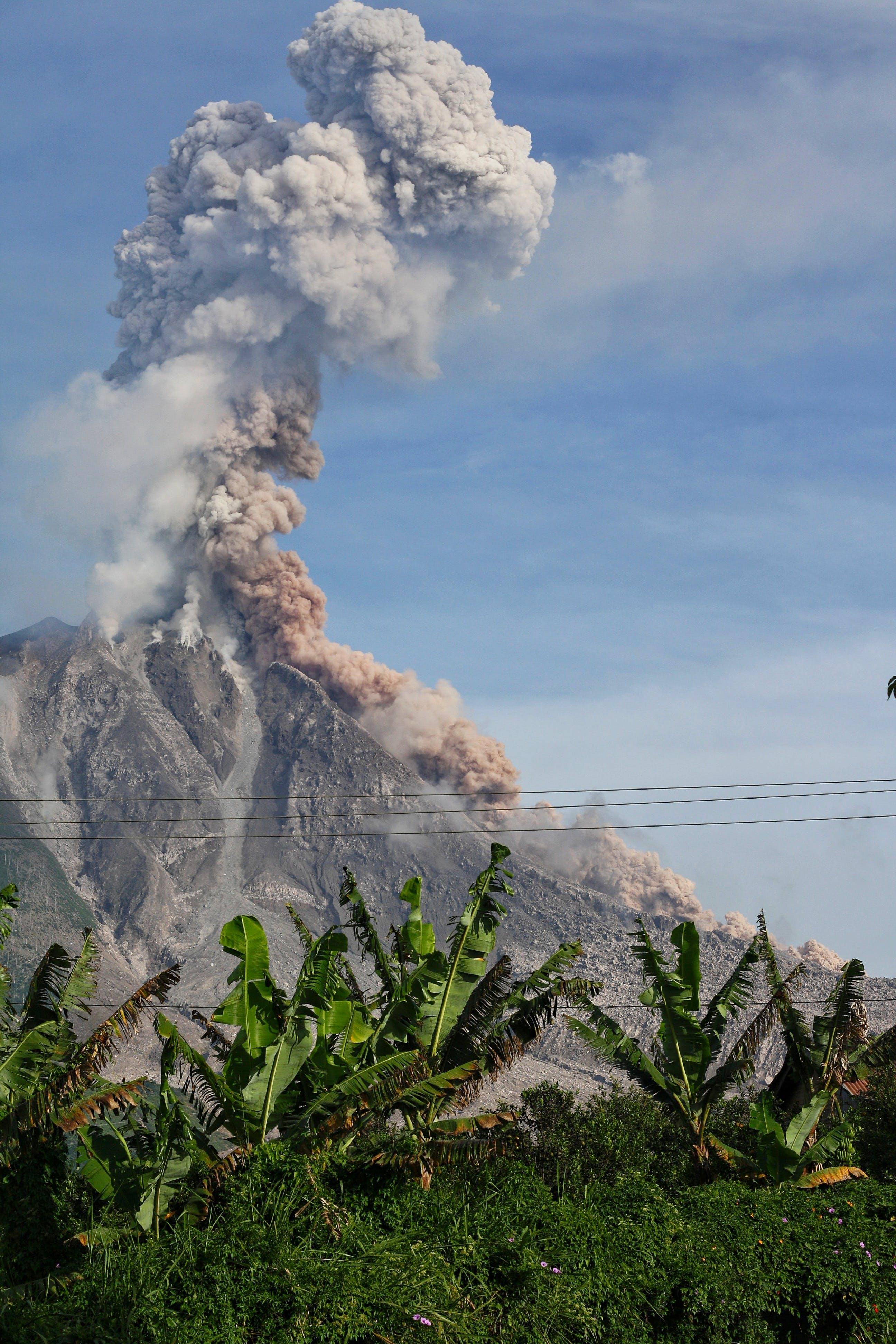 Erupting Volcano Under Blue Sunny Cloudy Sky