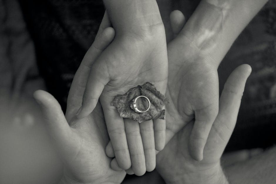 Person Holding Leaf and Ring in Grayscale