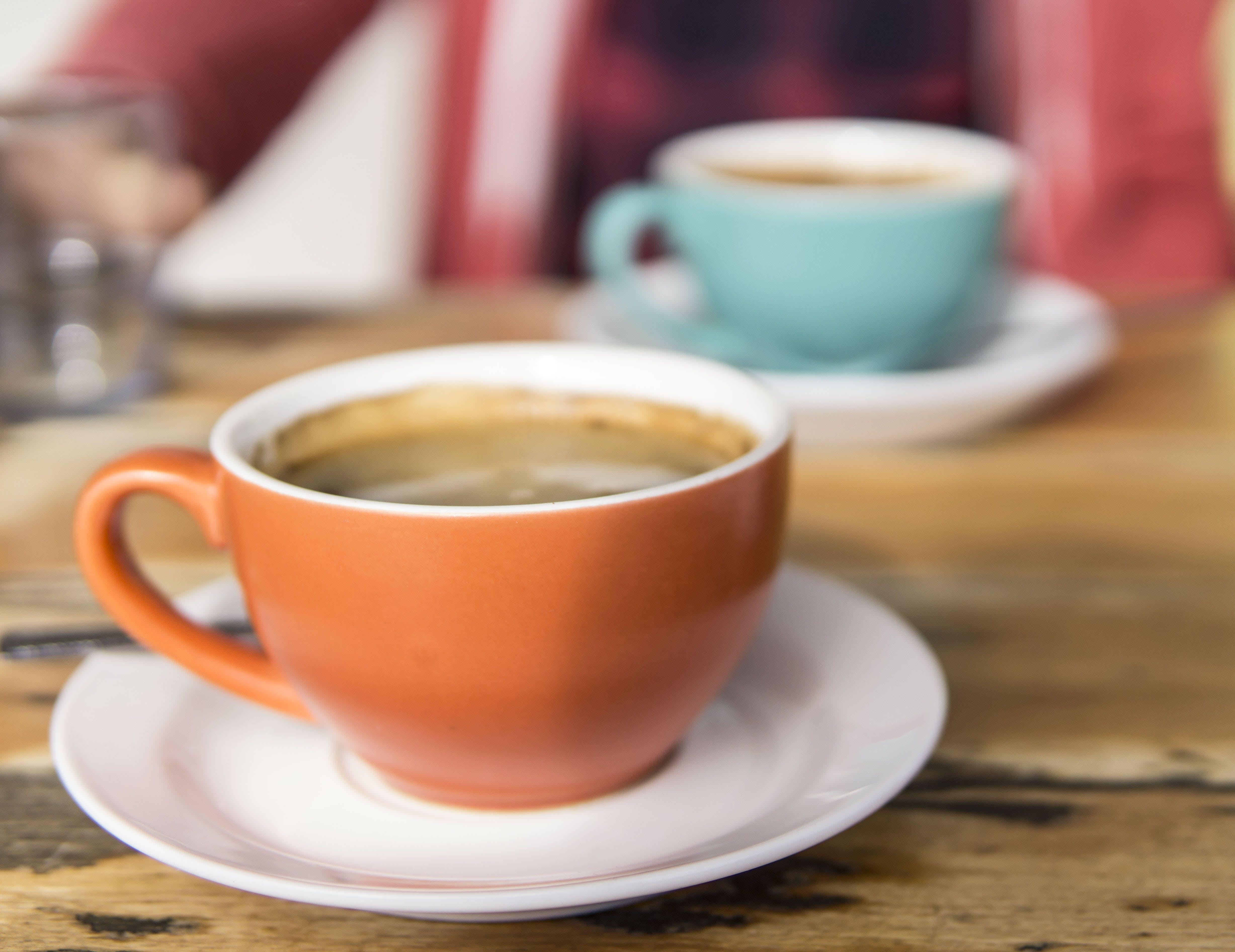 Shallow Focus Photo of Orange Ceramic Mug on White Saucer