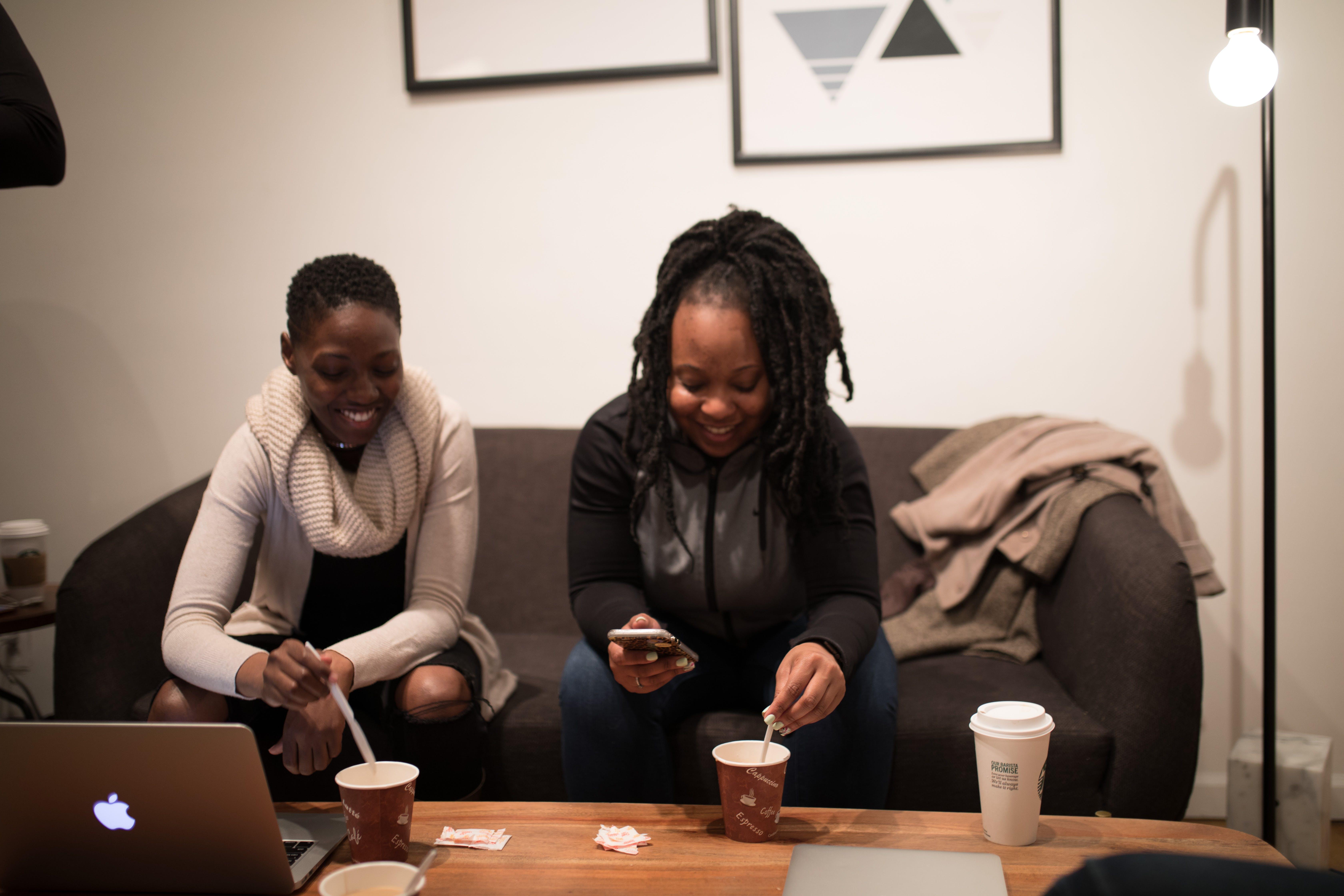 Woman in Black Jacket Sitting Beside Woman in White Sweater