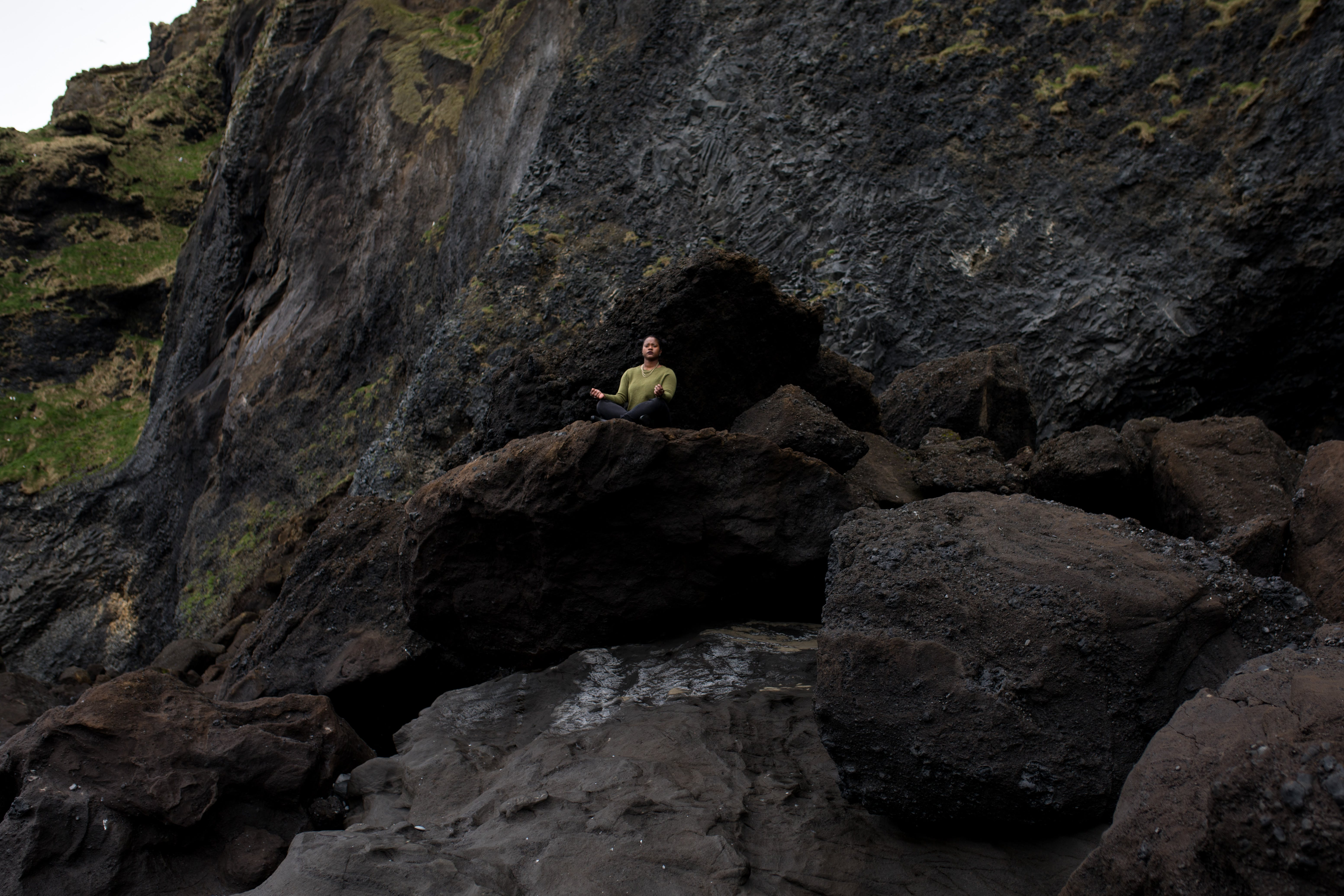 Photo of Person Meditating on Top of Rock