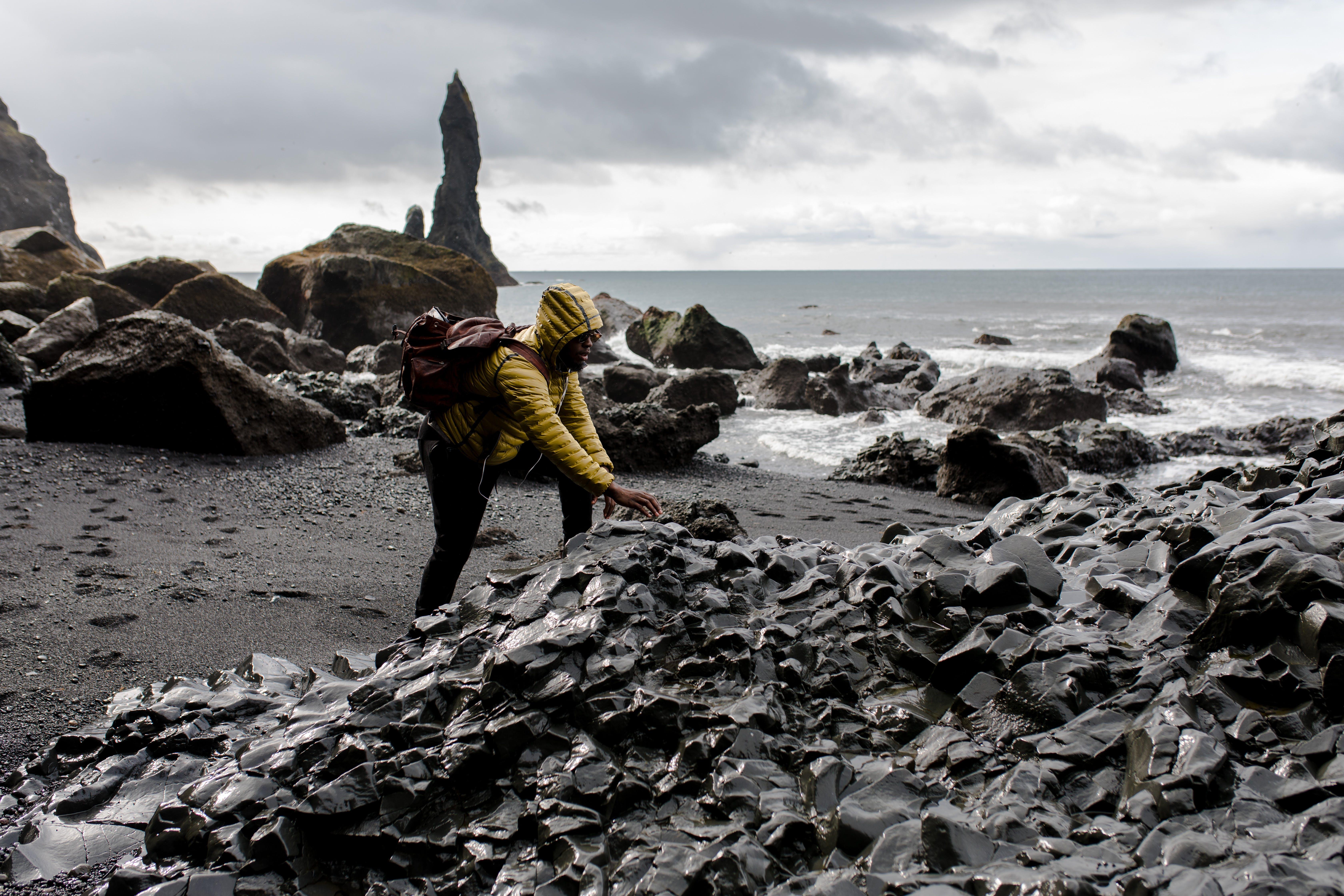 Person Wearing Hoodie Touching Stone in Seashore