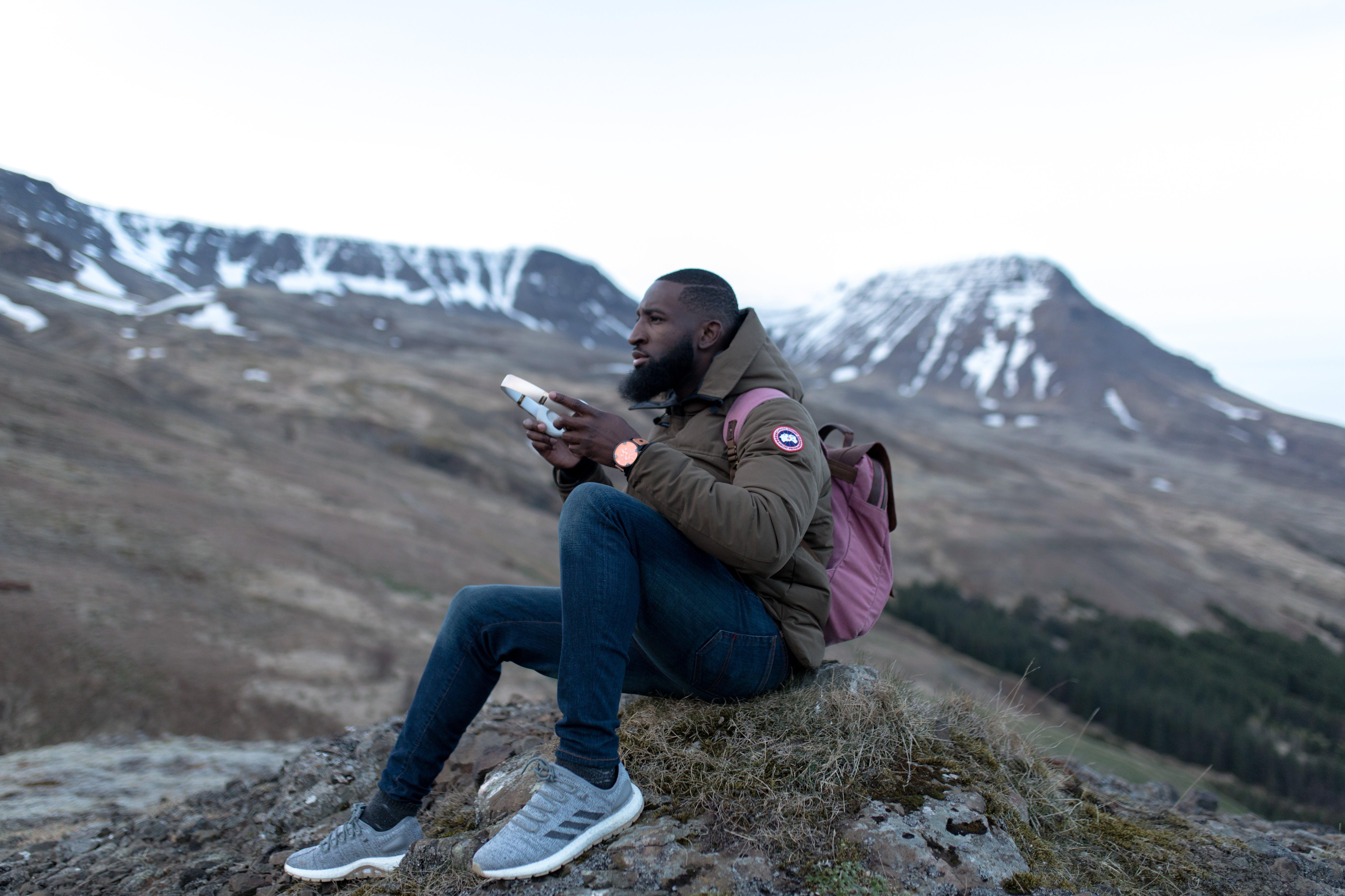 Man Wearing Brown Jacket and Blue Pants Sitting on Green Grass Holding Rectangular Case