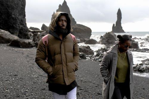 Man and Woman Wearing Jackets Walking on Shore