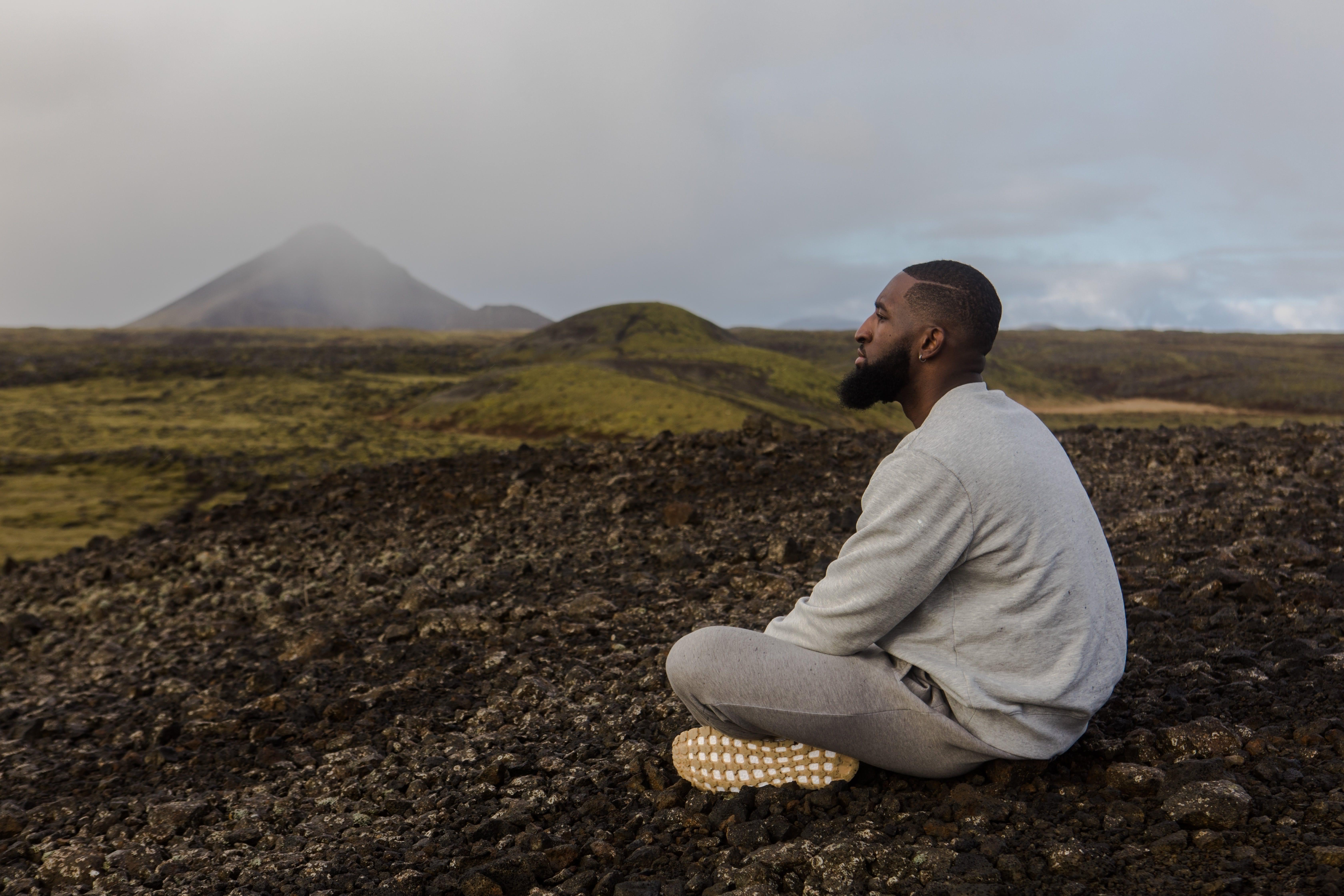 Man in White Top Sitting on Brown Soil