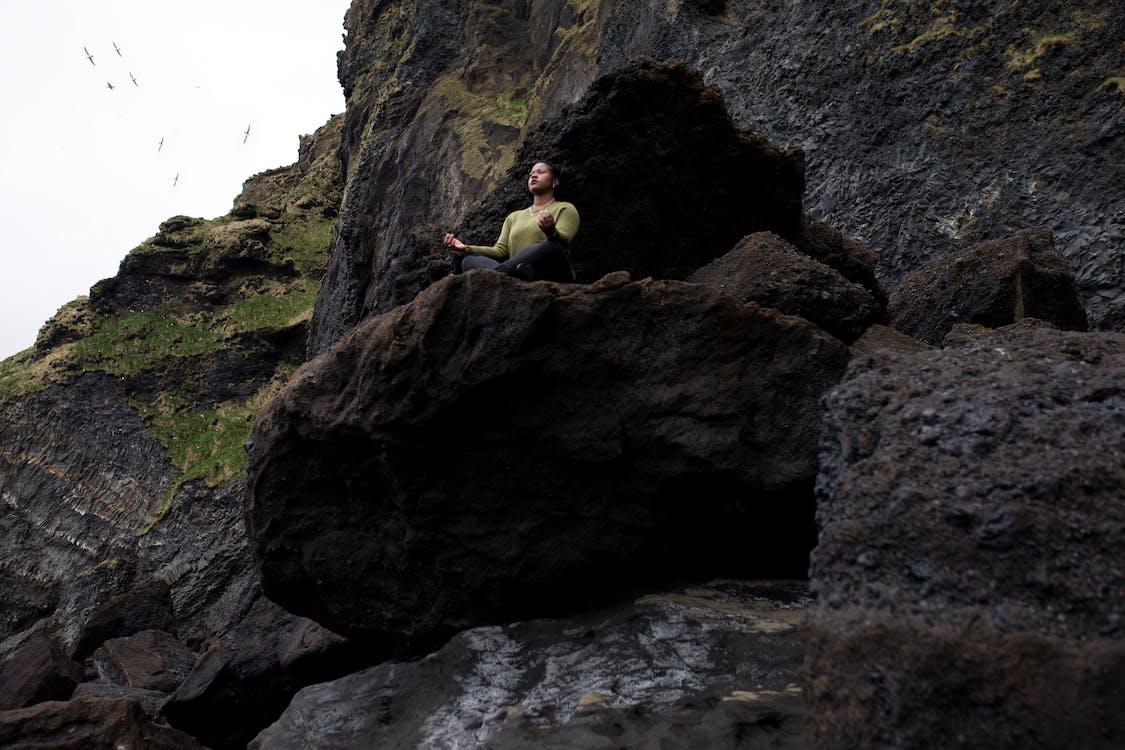 Person Doing Yoga on Rocky Mountain