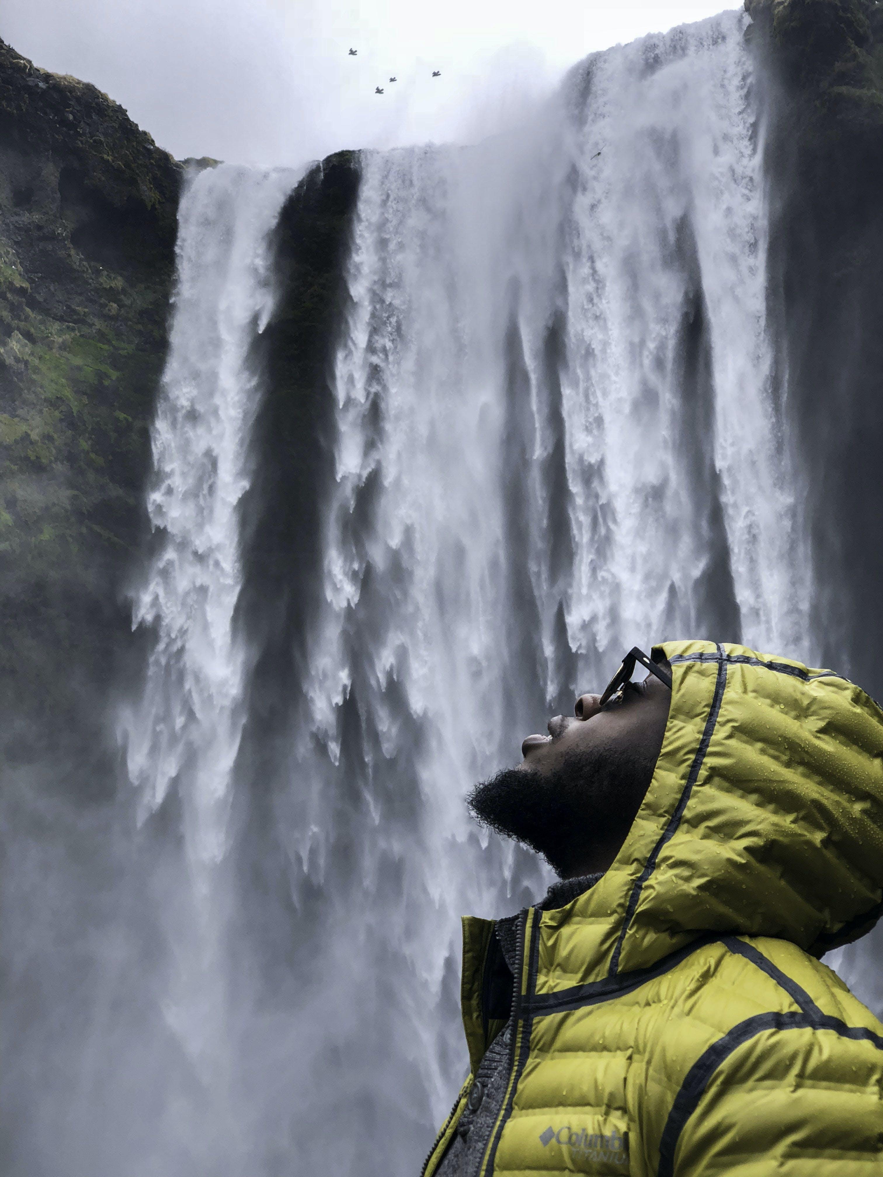 Photography of Man Wearing Bubble Hoodie Jacket Near Waterfalls