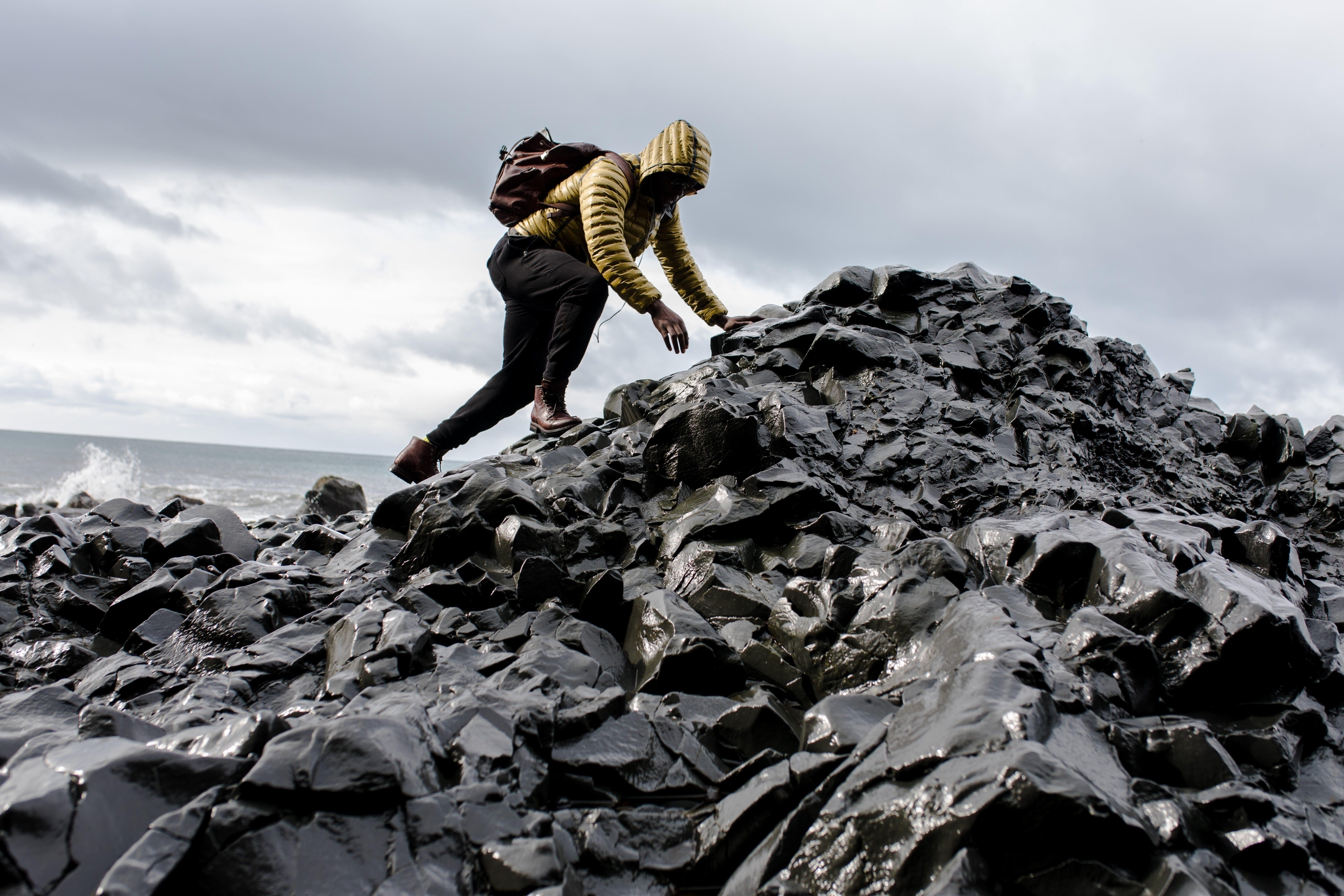 Man Wearing Hoodie and Black Pants Climbing Up Pile of Rocks