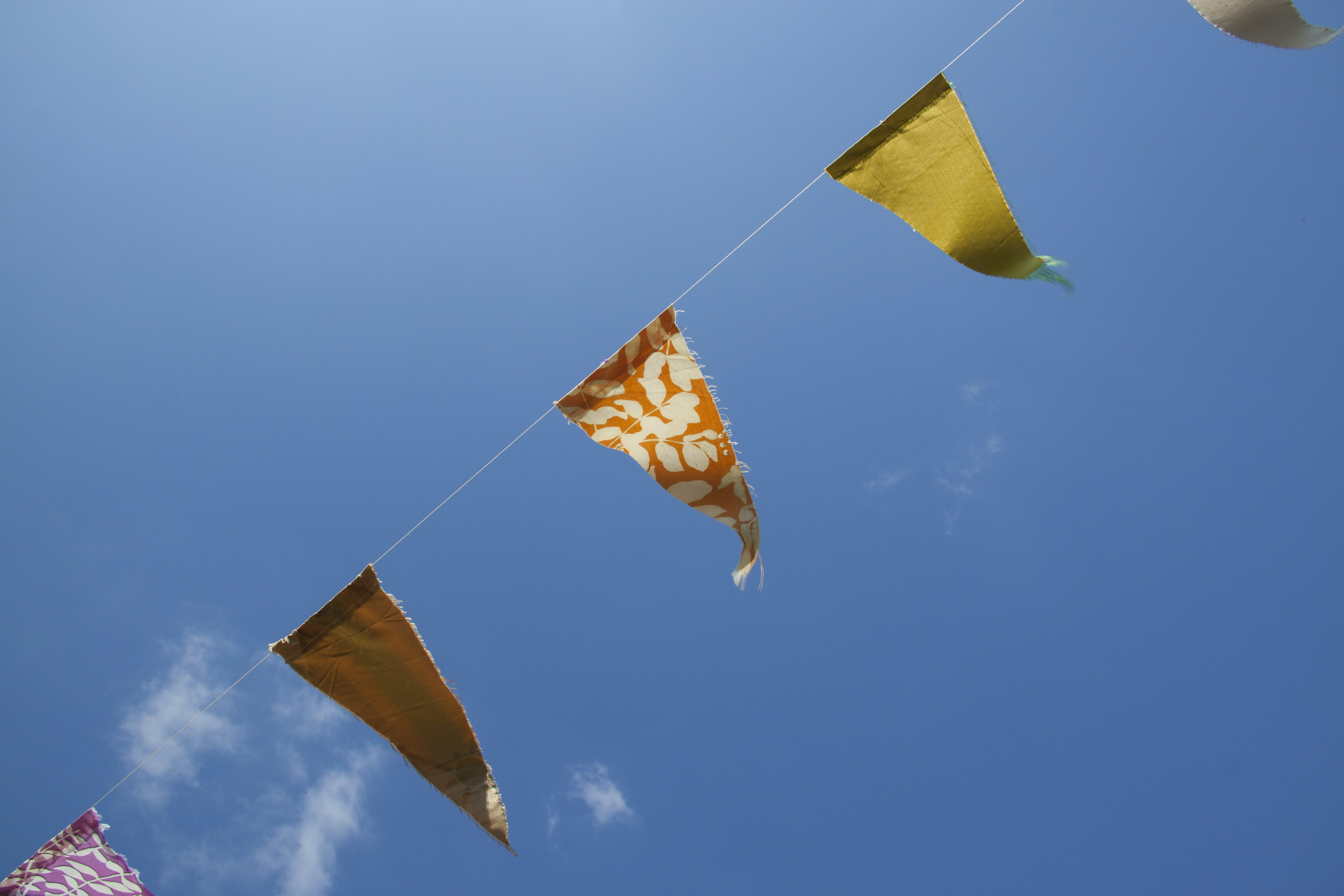Orange Yellow and Red Flaglets Under Blue White Sky during Daytime