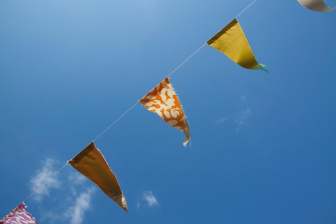 Oranjegele En Rode Vlaggetjes Onder Blauw Witte Hemel Overdag