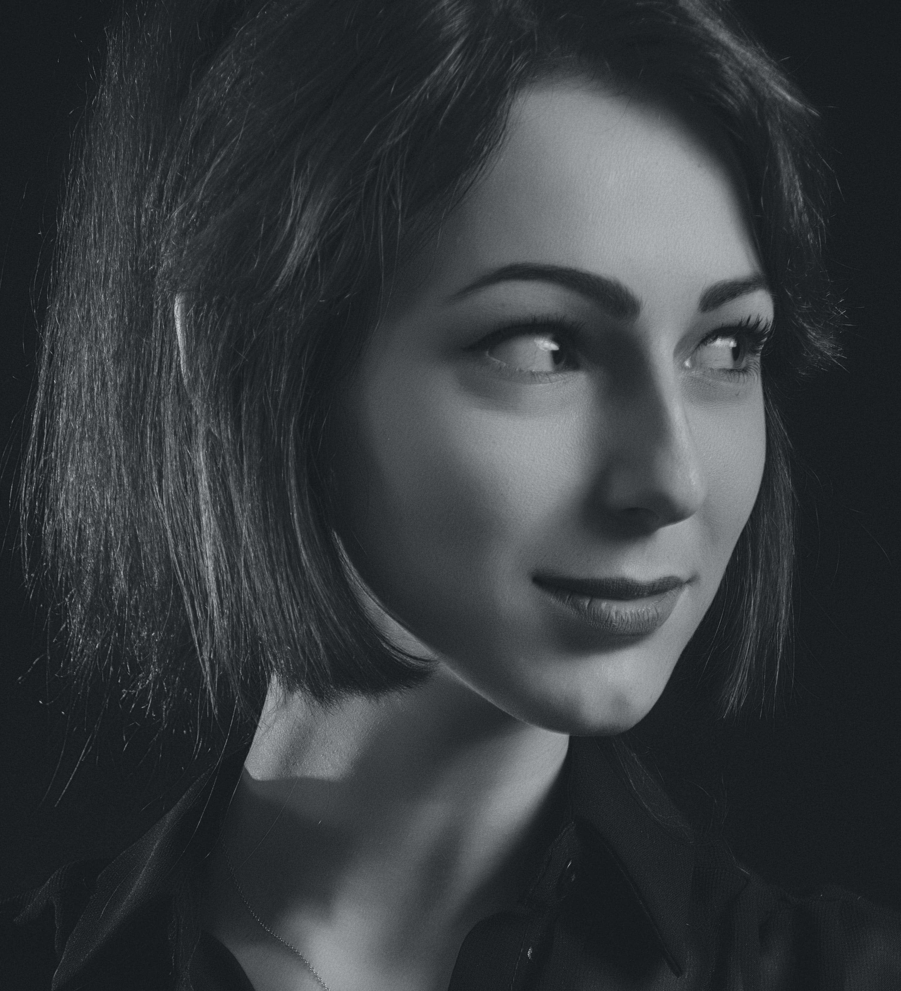 Grayscale Photo of Woman Wearing Collared Shirt Looking Sideways