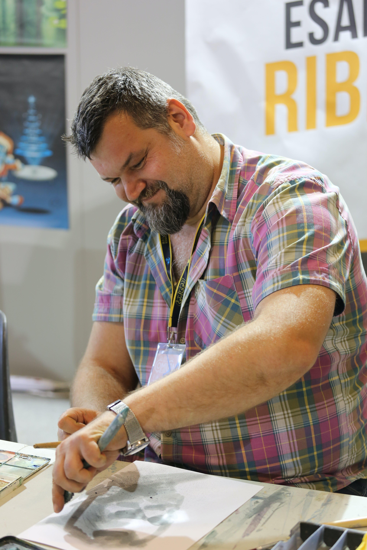 Man Wearing Pink Checkered Shirt While Sketching