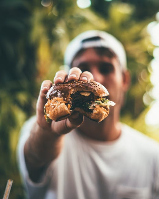 Photo of Person Holding Burger