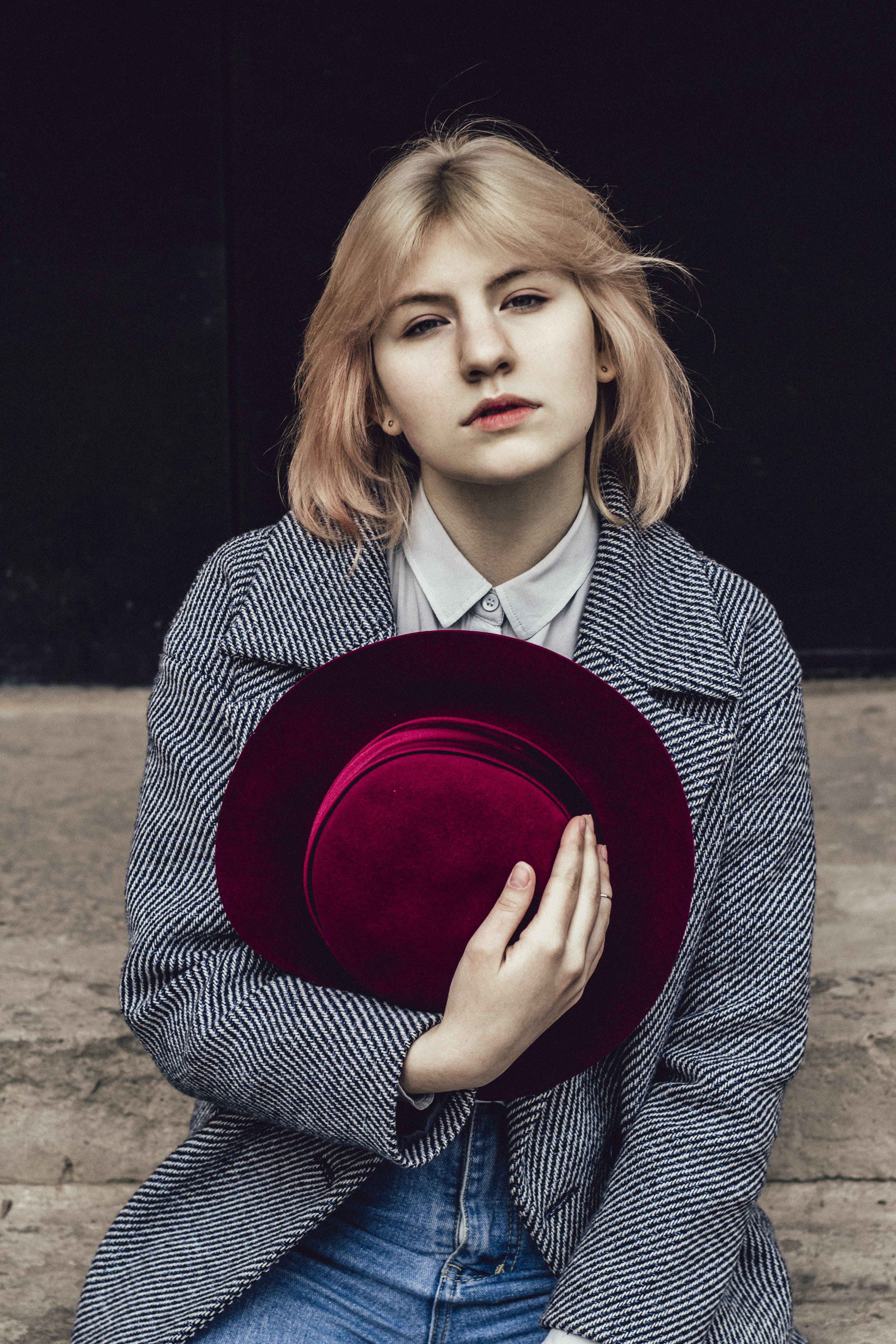 Woman in White Collared Top and Gray Coat Holding Red Fedora