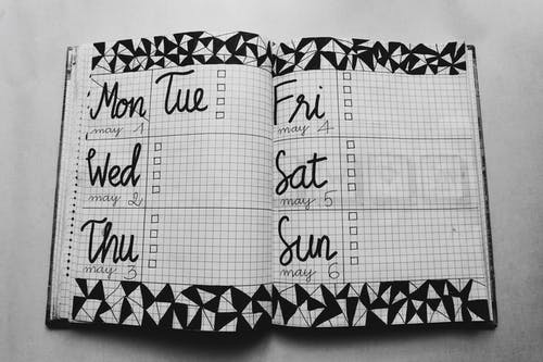 White and Black Weekly Planner on Gray Surface
