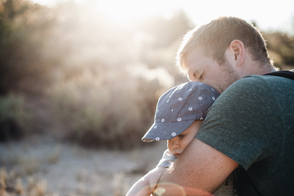 Man Hugging the Baby in Blue Floral Fitted Cap during Daytime