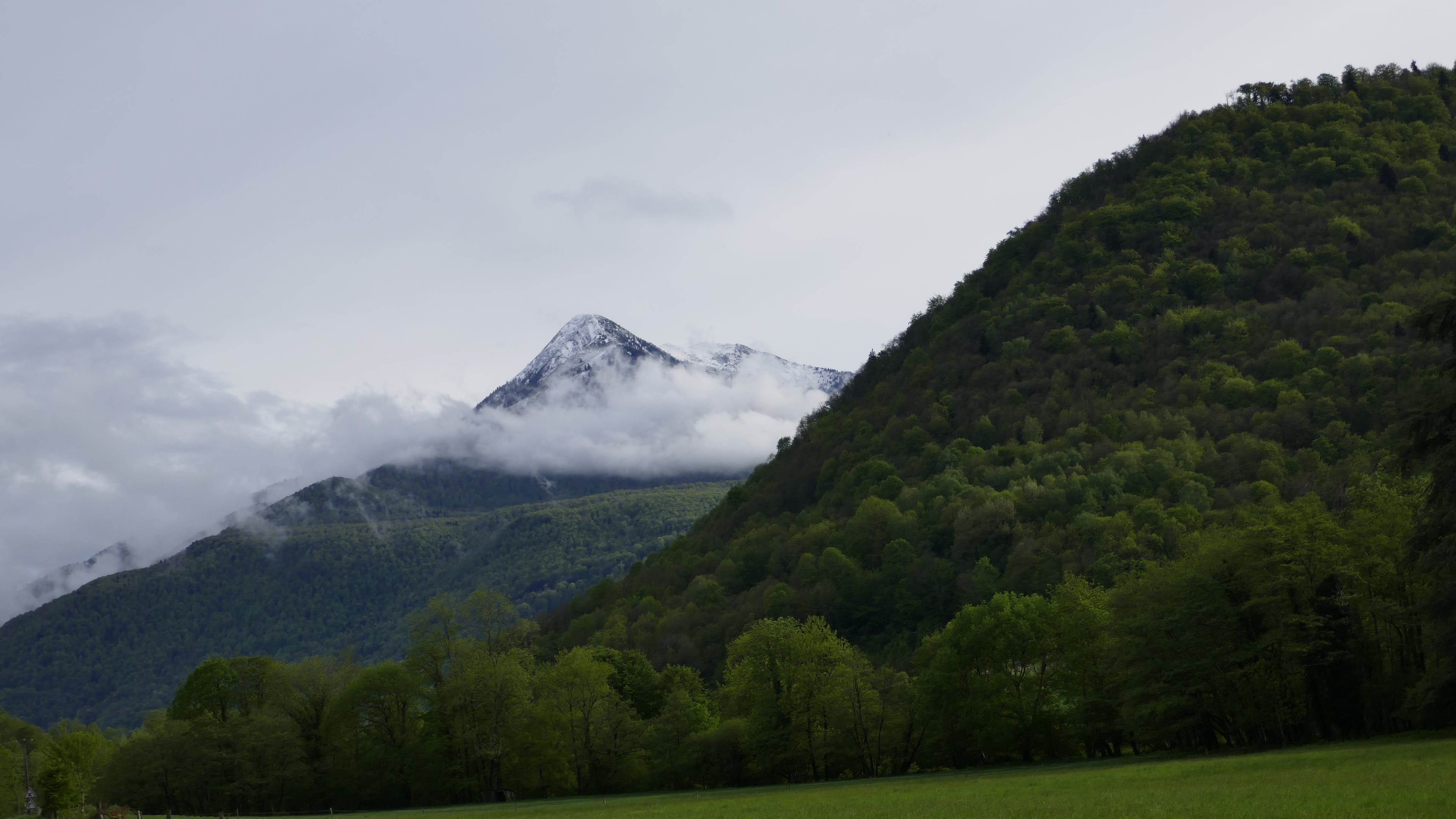 hill next to a mountain Surrounded by Clouds