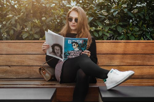 Photo of Woman Sitting on Wooden Bench While Reading Magazine