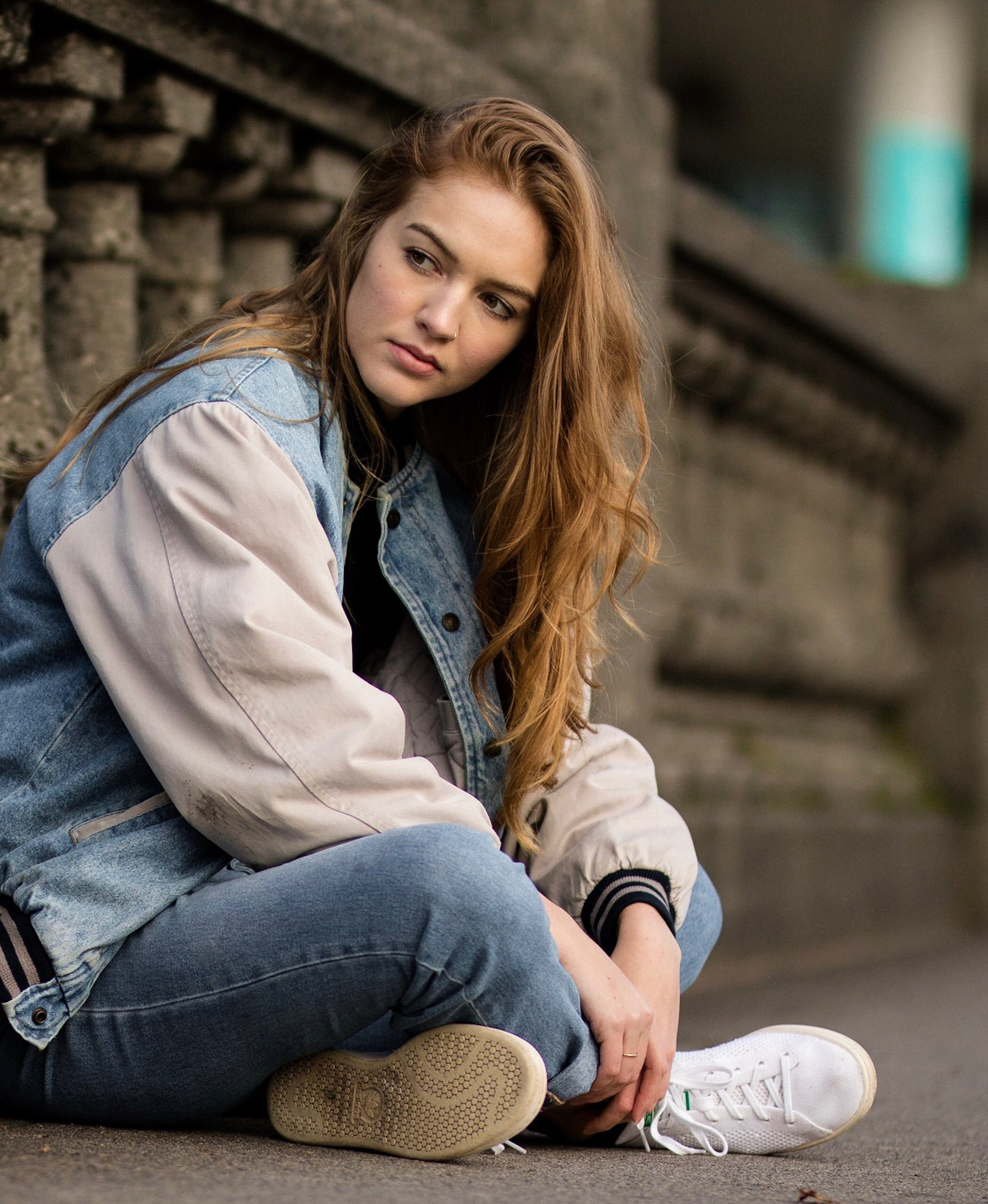 Brown Haired Woman Sitting Beside Gray Concrete Railings