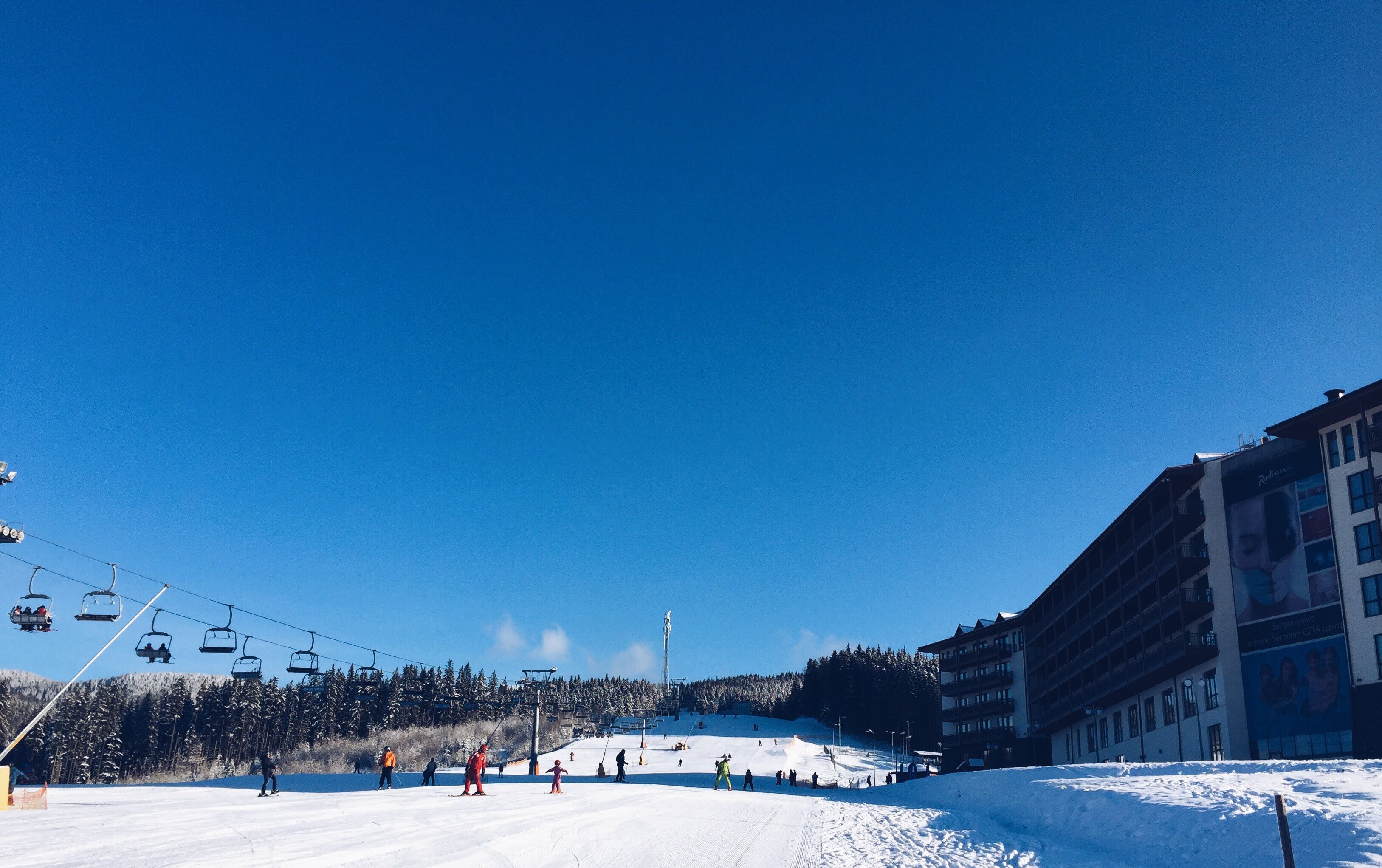 People on a Snowy Ski Hill With a Lift on the Left and a Hotel on the Right